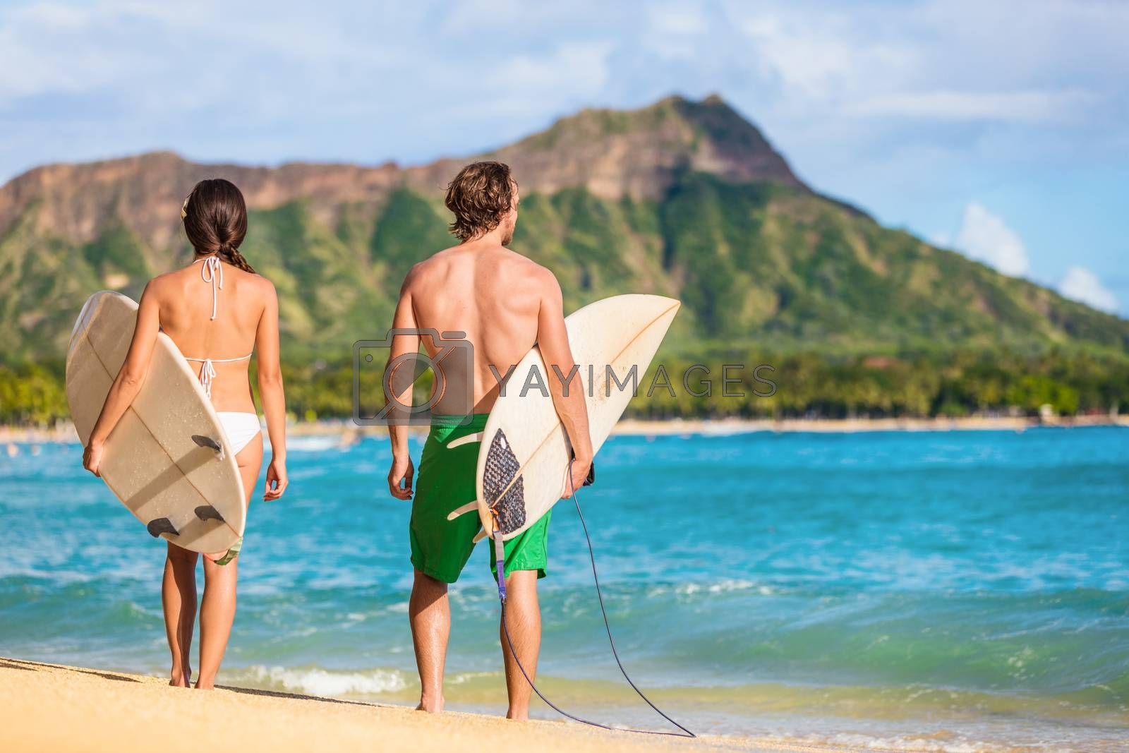 Hawaii surfers people relaxing on waikiki beach with surfboards looking at waves in Honolulu, Hawaii. Healthy active lifestyle fitness couple at sunset with diamond head mountain in the background by Maridav
