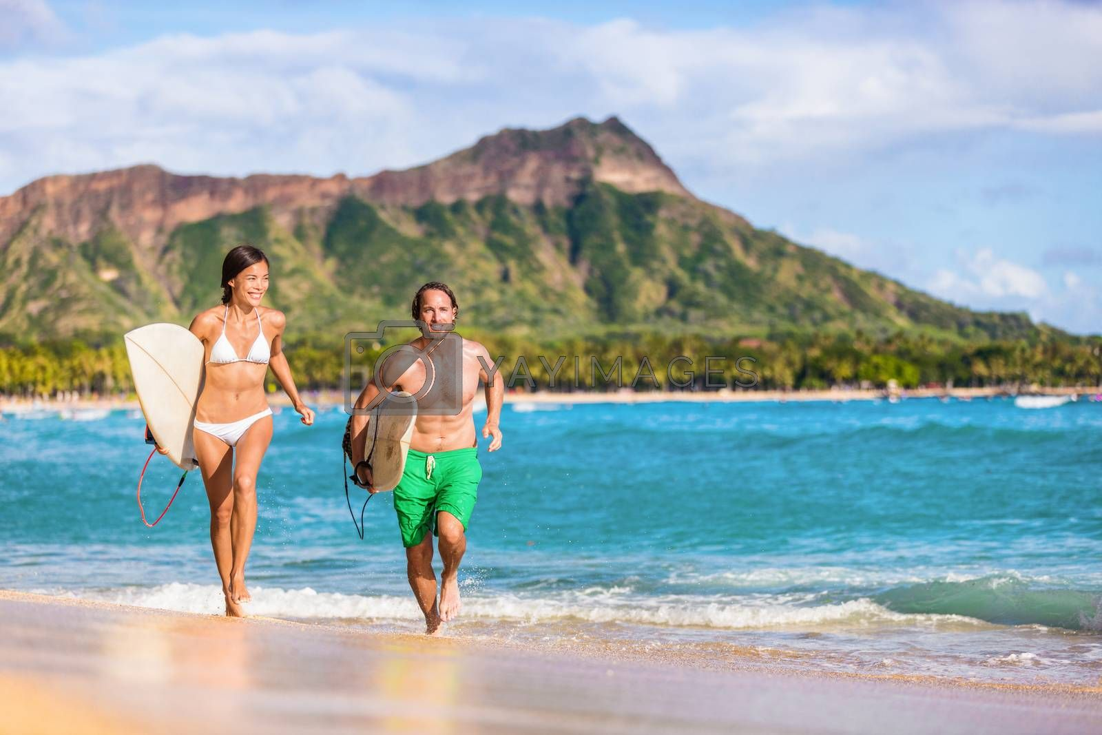 Happy surf people having fun surfing on Waikiki beach, Honolulu, Oahu, Hawaii. Asian woman, caucasian man multiracial couple running out of ocean splashing water. Summer vacations travel landscape by Maridav