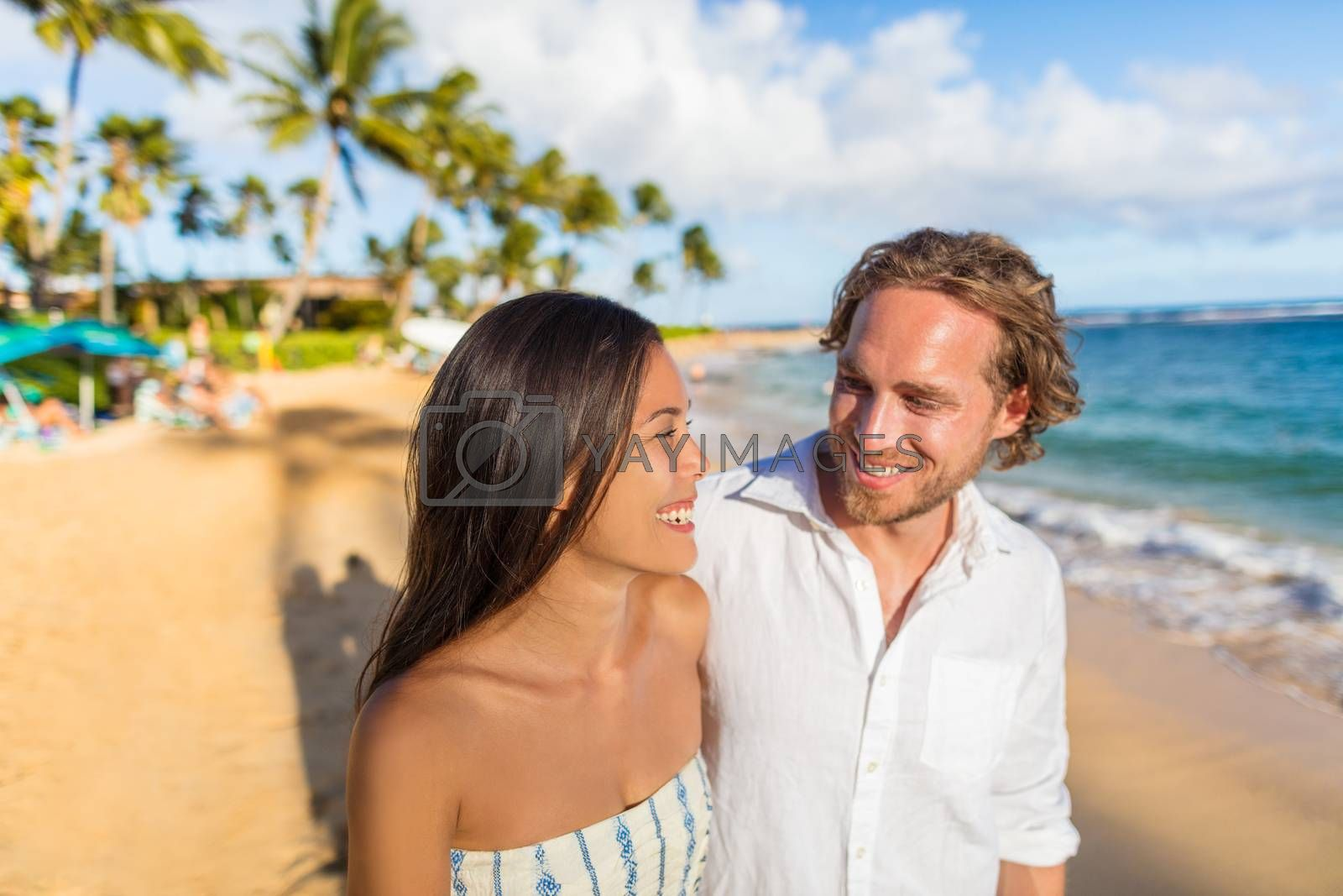 Hawaii travel beach couple laughing together happy on honeymoon vacation. People enjoying hawaiian sunset holidays by Maridav