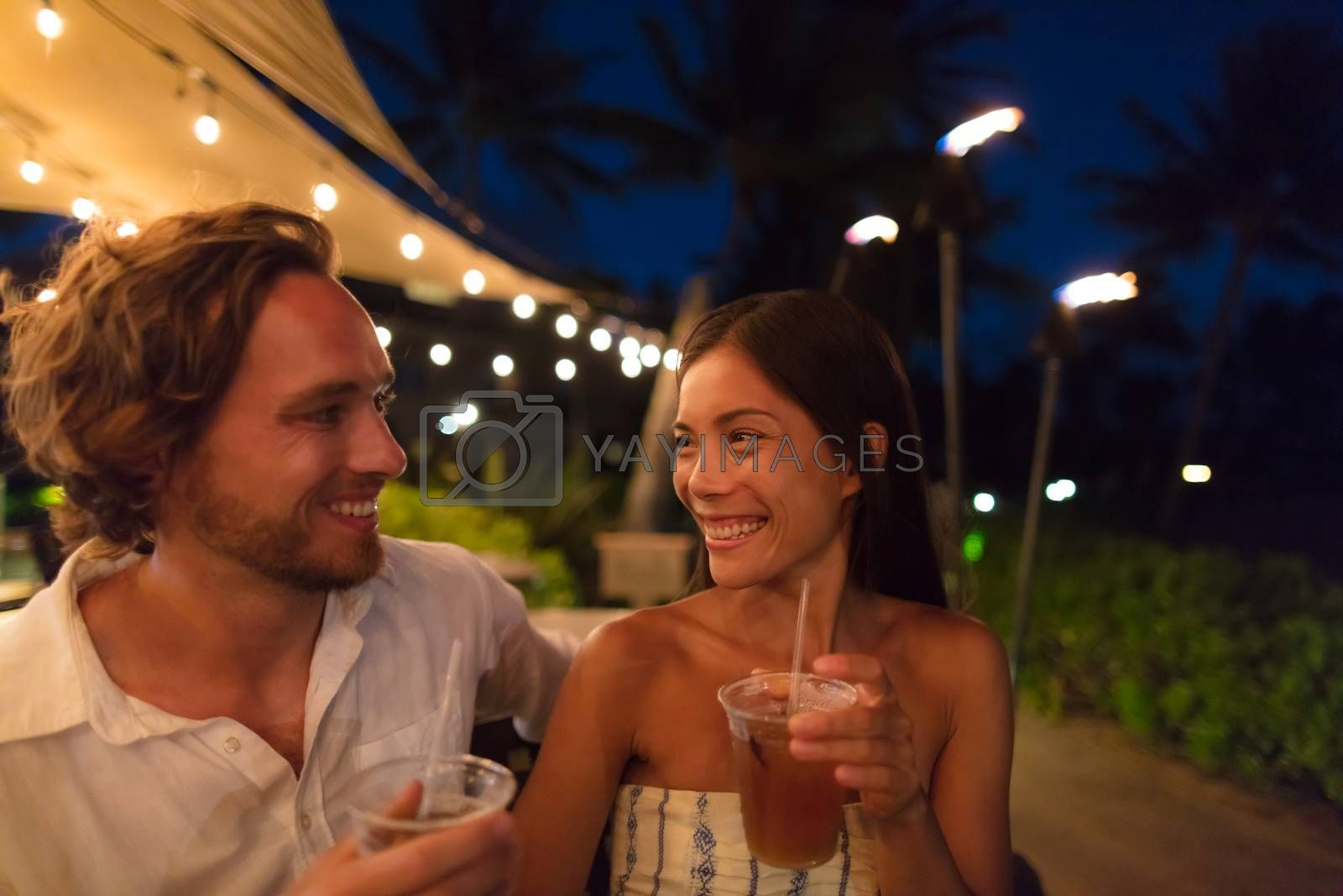 Couple dating drinking at bar on night out at outdoor restaurant terrace in Hawaii vacation travel. Asian woman, man having fun together toasting mai tai drinks, hawaiian cocktail. Luxury lifestyle by Maridav