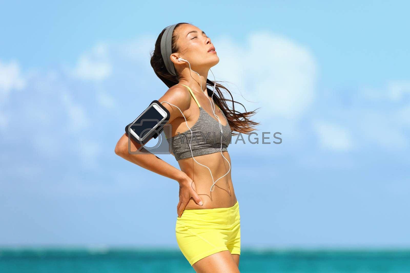 Tired woman runner on morning training at beach exhausted breathing listening to music with headphones and armband for smartphone. Heat exhaustion / dehydration concept.