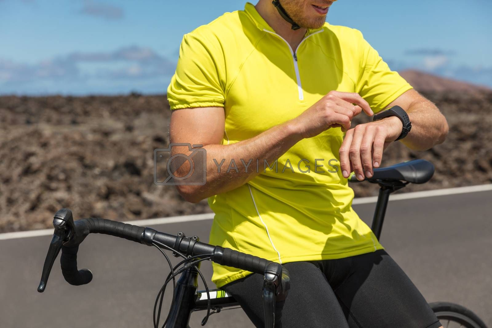 Athlete cyclist using an activity tracker gps smartwatch during biking workout training. Road bike sports man using his watch app for fitness tracking. Healthy lifestyle.