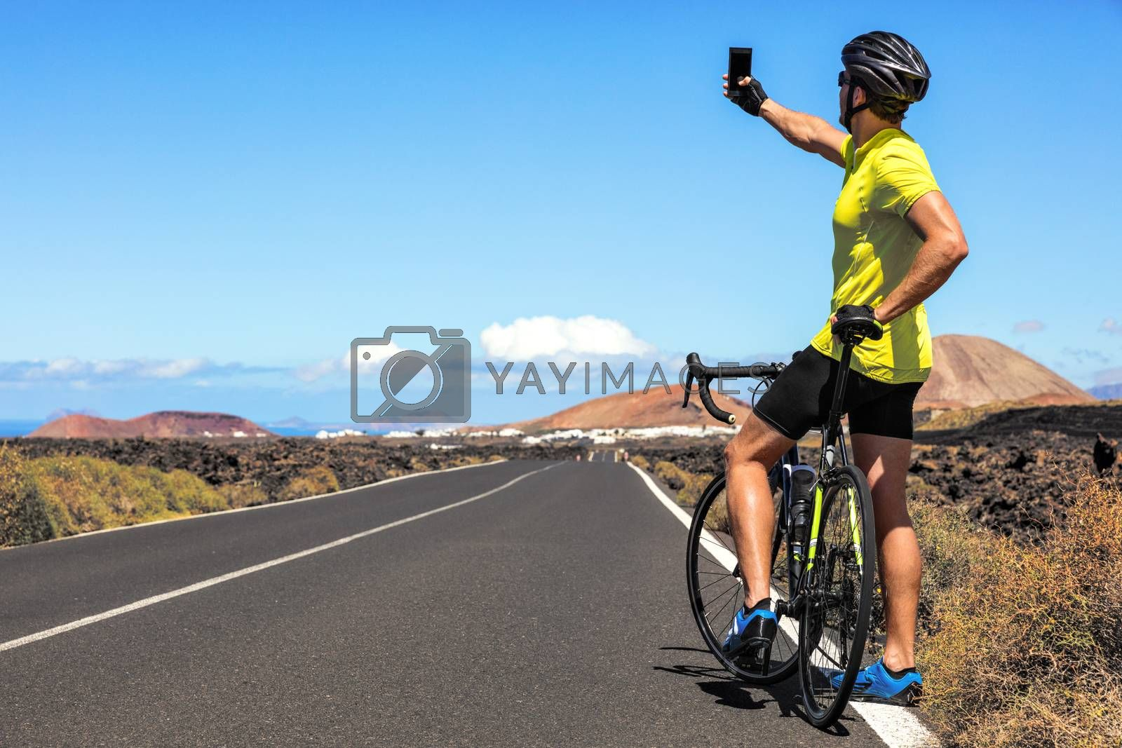 Cyclist tourist taking selfie picture with smartphone during biking trip alone on summer vacation travel. Man riding road bike using phone to take photos during holidays.