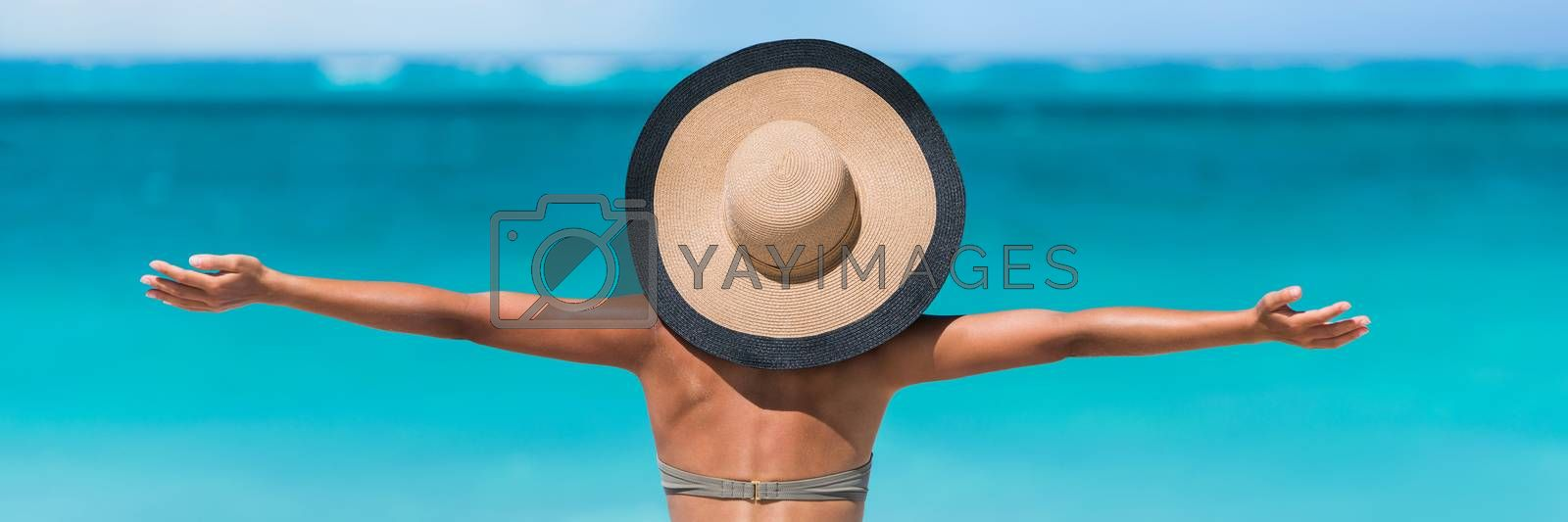 Beach vacation freedom summer travel holidays banner panorama. Woman in sun hat and bikini with open arms raised to the sky enjoying looking view of beach blue ocean.