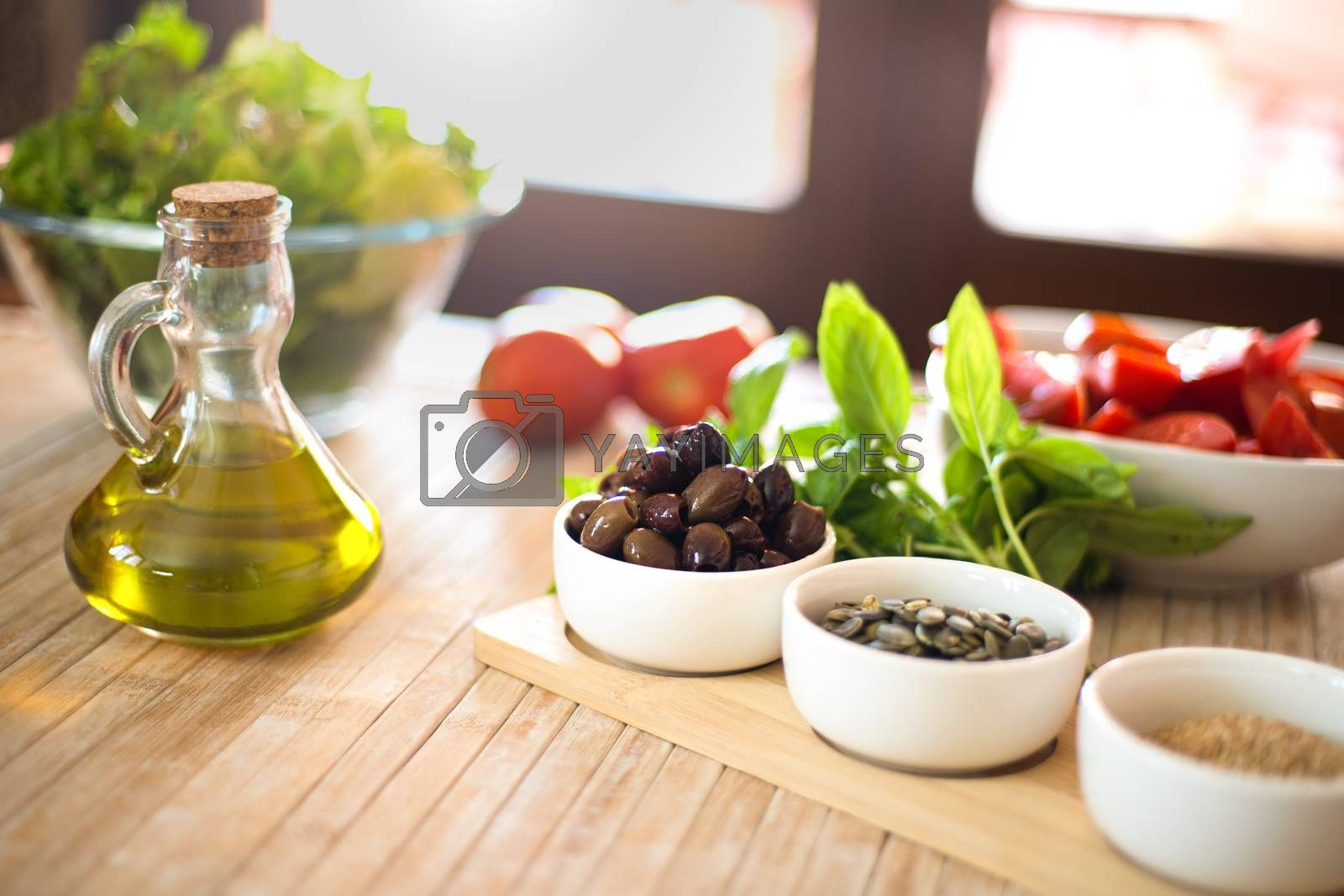 Extra virgin olive oil and olives in the foreground with fresh vegetables and sunlight in the background - Mediterranean diet concept - Healthy summer food concept