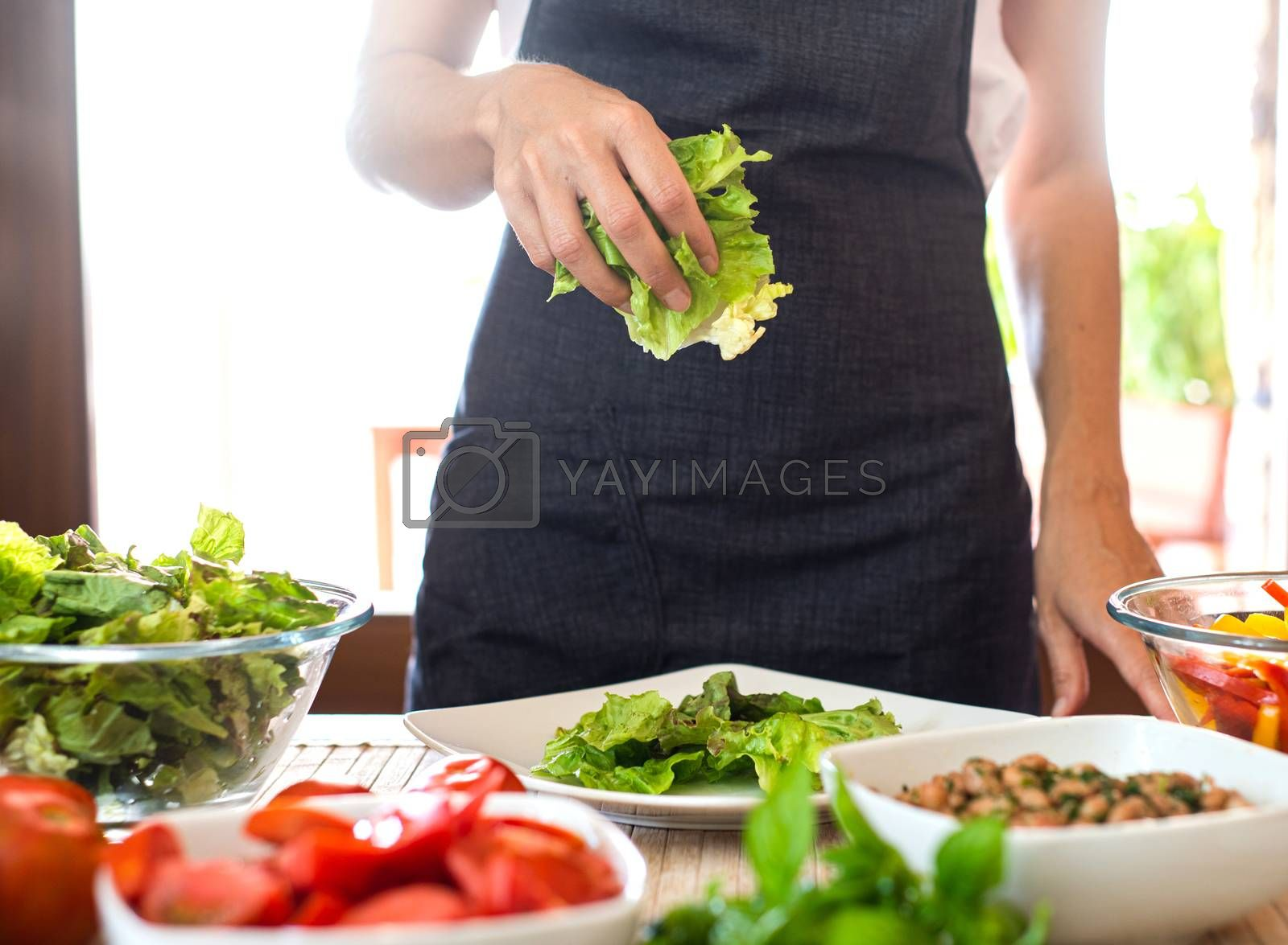 Woman chef preparing a fresh salad at home with sunlight in background with lettuce, tomatoes, beans, seeds on the table - Healthy vegan and vegetarian food concept