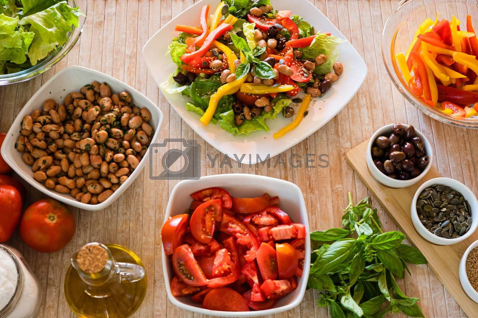 Flat lay top view of a compound fresh salad plate with vegetable ingredients all around it on a light wooden table and natural sunlight - Fresh healthy vegan food concept