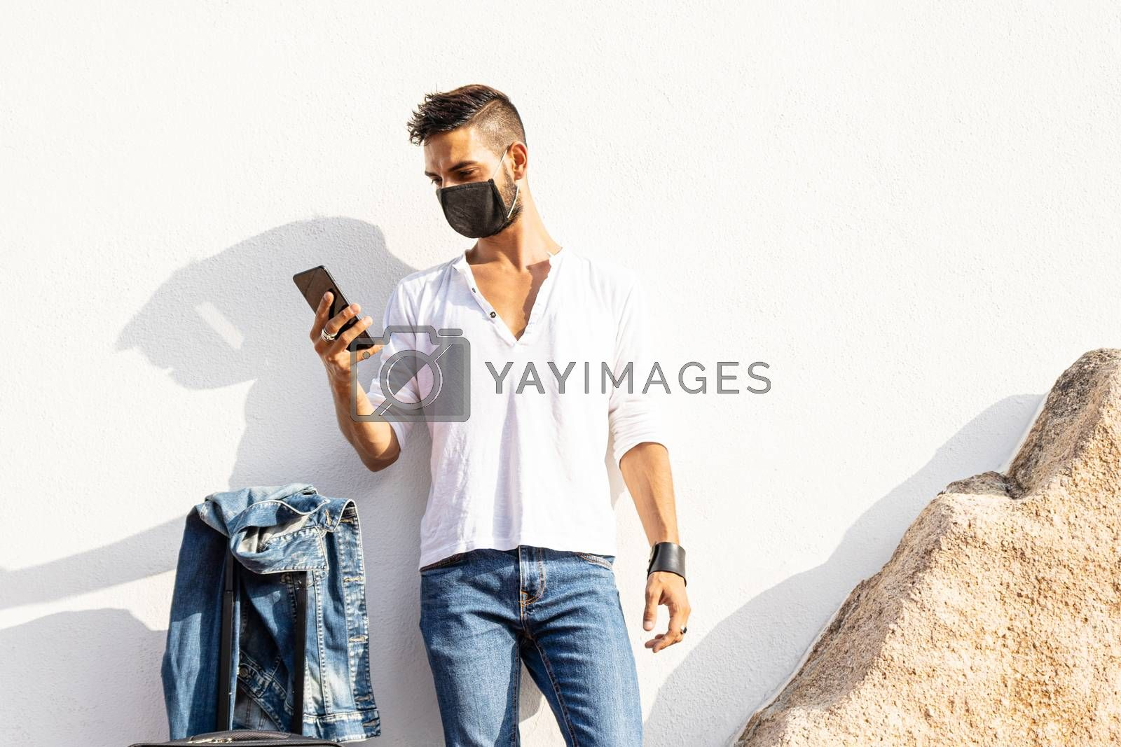 Stylish millennial boy standing to a white wall with COVID protection mask using his smartphone - Solo traveller safe concept - Connected young man communicating with technology