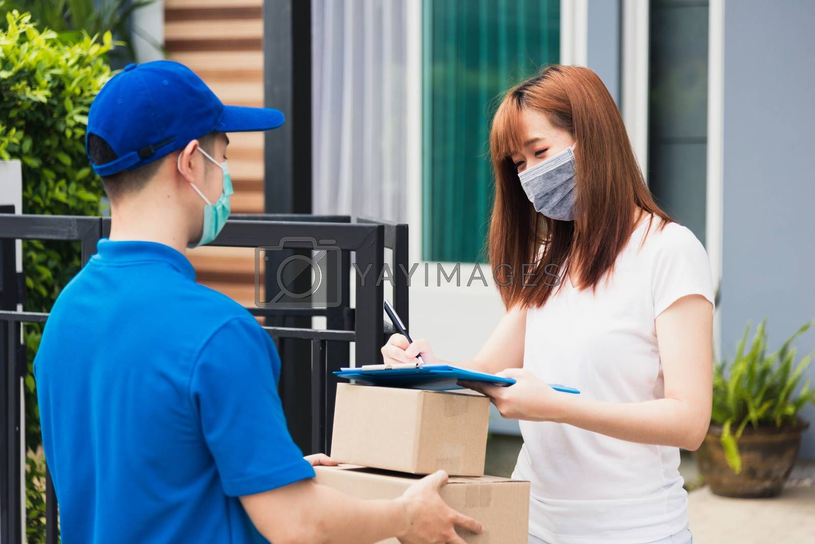 Asian young delivery man with package post boxed he protective face mask service woman customer using pen signature on paper book at front home, under curfew quarantine pandemic coronavirus COVID-19