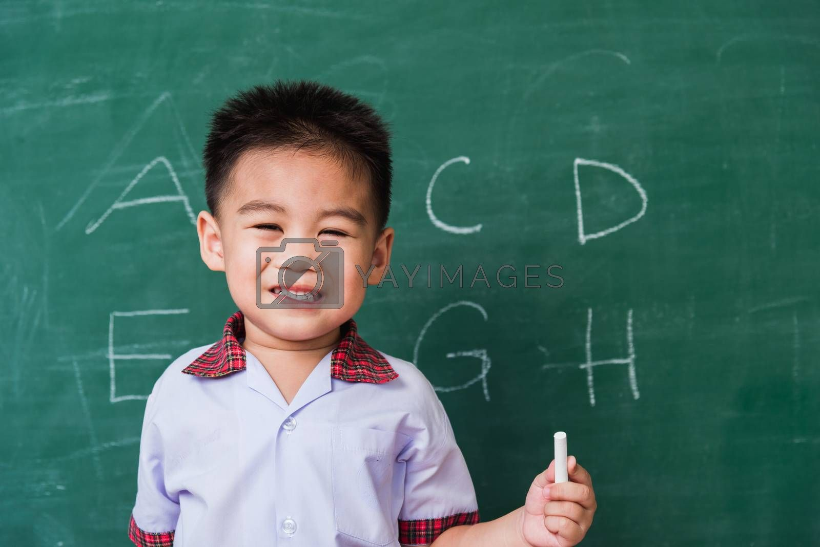 Back to School. Happy Asian funny cute little child boy kindergarten preschool smile in student uniform hold white chalk after write ABC with on green school blackboard, First time to school education