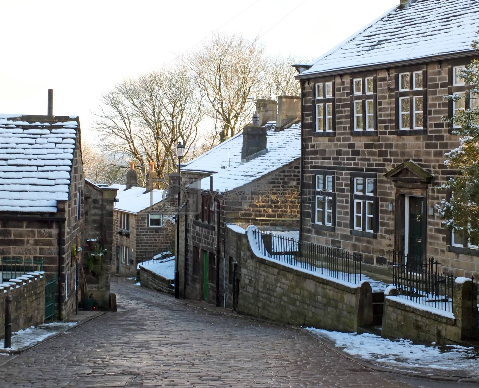A scenic view of the main street in the village of heptonstall in west yorkshire with snow covering the old stone houses and pennine scenery visible in the background by Philip Openshaw
