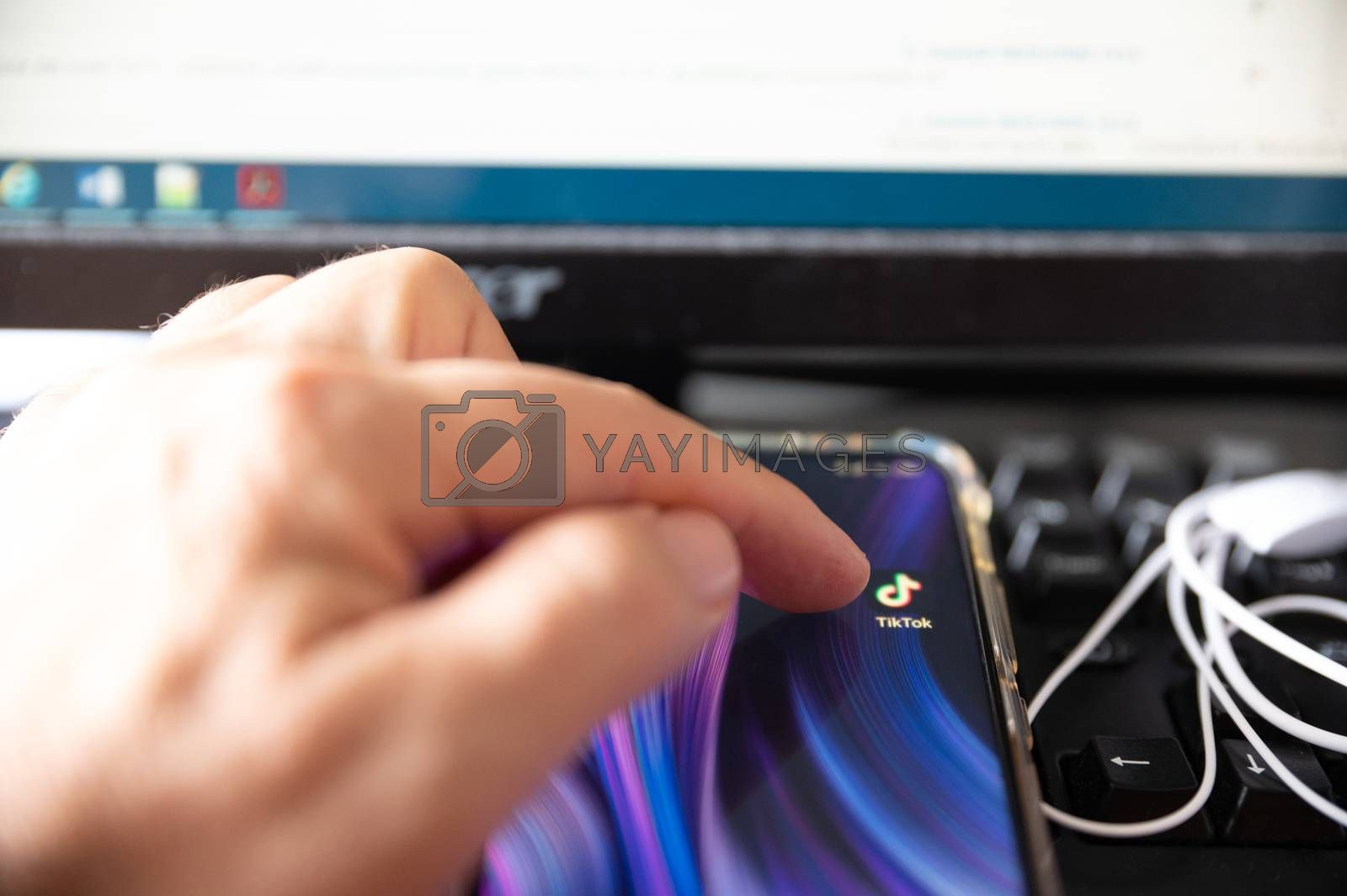 Turin, Piedmont, Italy. July 2020. Against the background of a workplace, close-up image of the smartphone display: the logo of the Tik Tok application is highlighted, the finger is about to touch it.