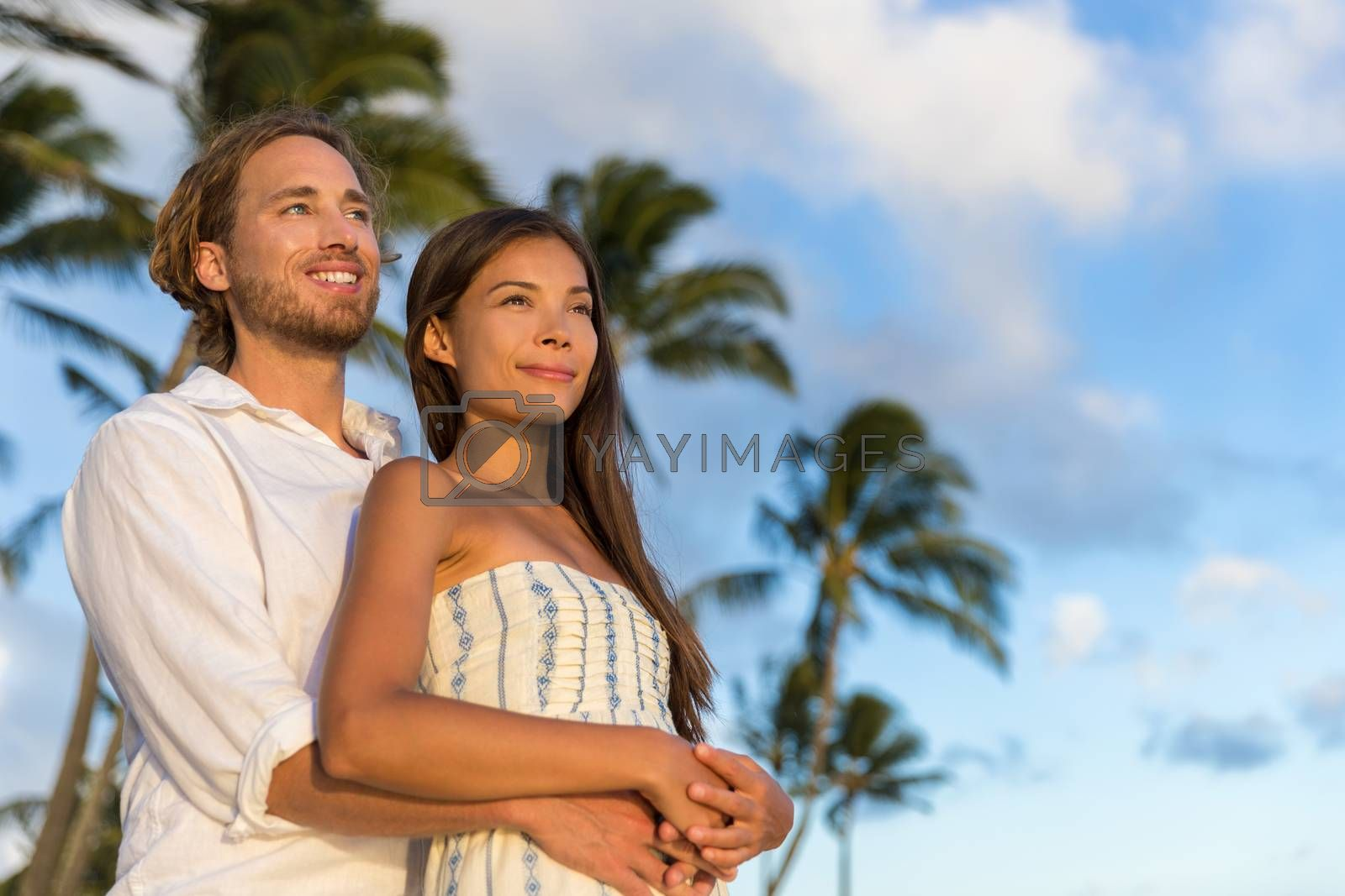 Relaxing couple watching sunset on summer travel vacations. multiracial people enjoying tropical holiday together hugging in love.