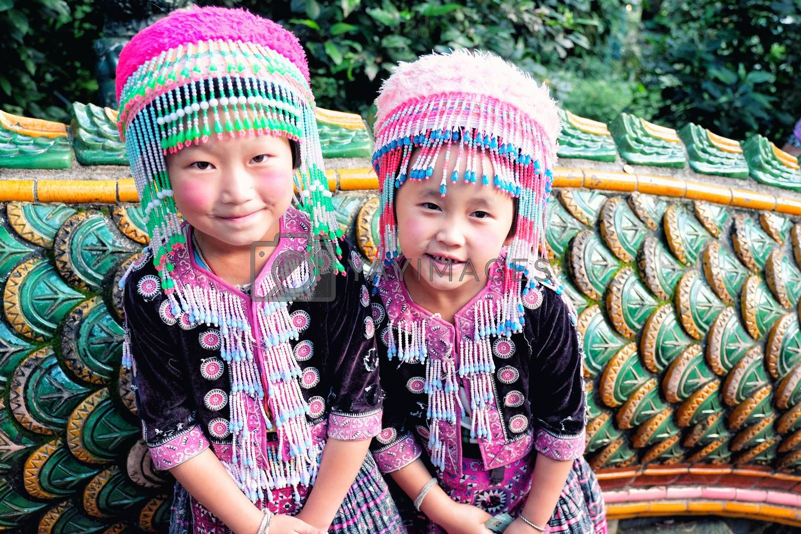 CHIANGMAI, THAILAND - NOVEMBER 13, 2016 : Little hill tribe girls waiting for tourist to take a picture with them at mythological nagas staircase to Doi Suthep Temple in Chiang Mai, Thailand