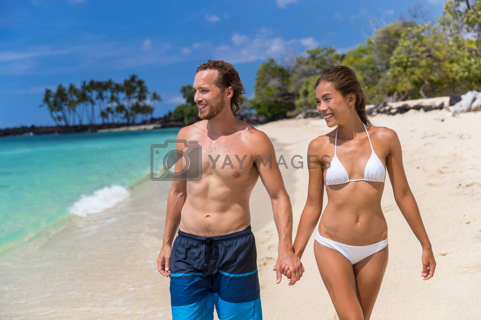 Beach bikini couple enjoying summer vacation travel holding hands on Hawaii tropical holidays. Sexy multiracial people with toned abs body.
