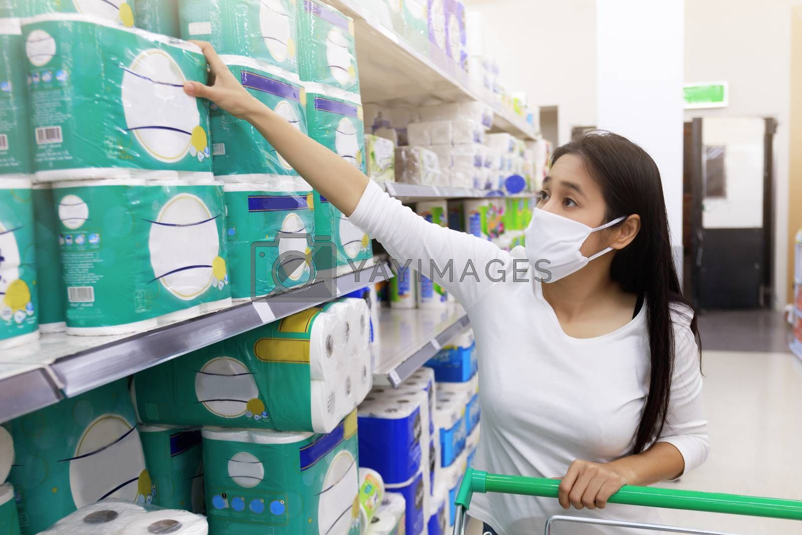 Asian woman wear face mask push shopping cart in supermarket. Gi by Satrinekarn