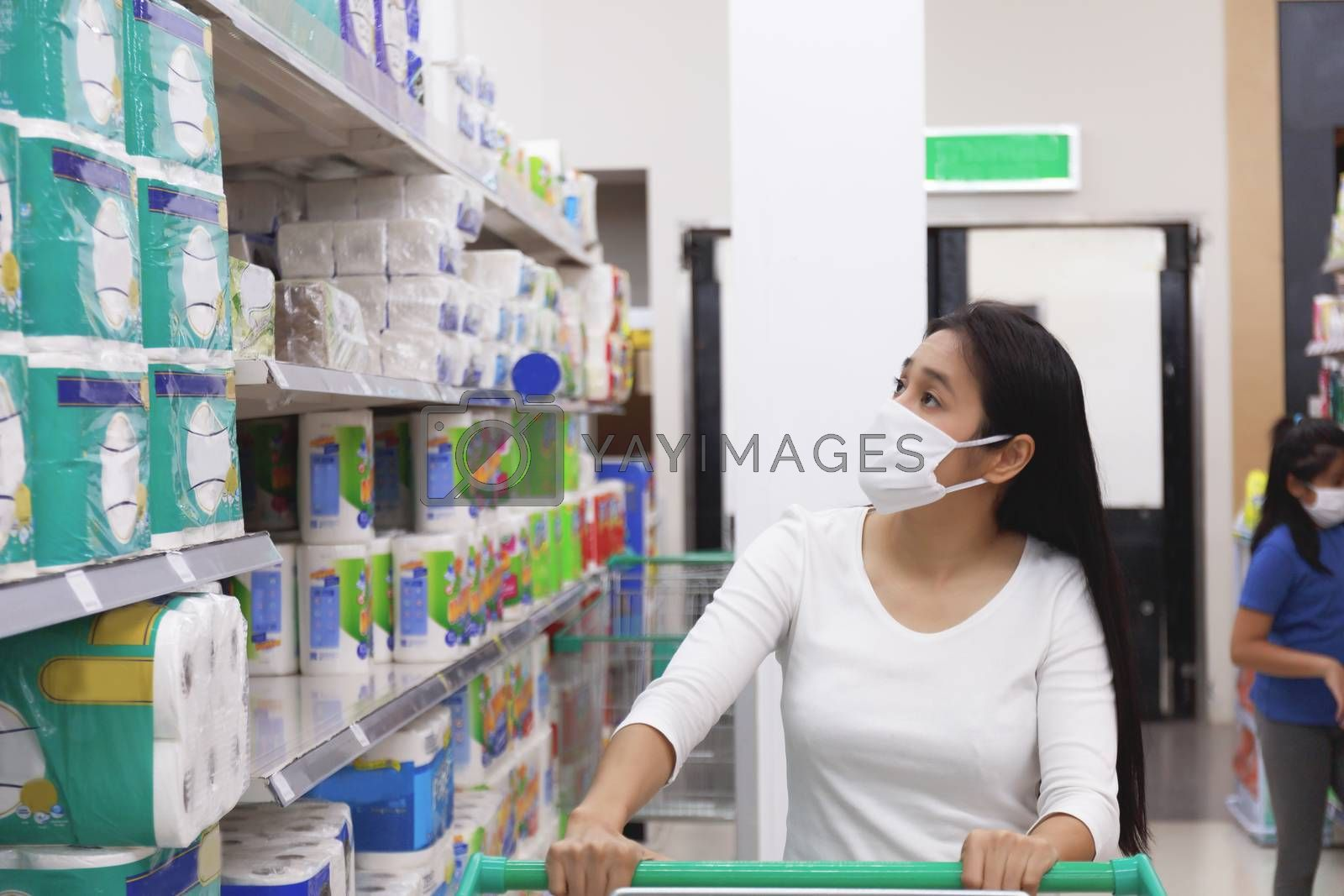 Asian woman wear face mask push shopping cart in supermarket. Girl looking grocery to buy something During coronavirus crisis or covid19 outbreak. Women wearing protective face mask new normal concept