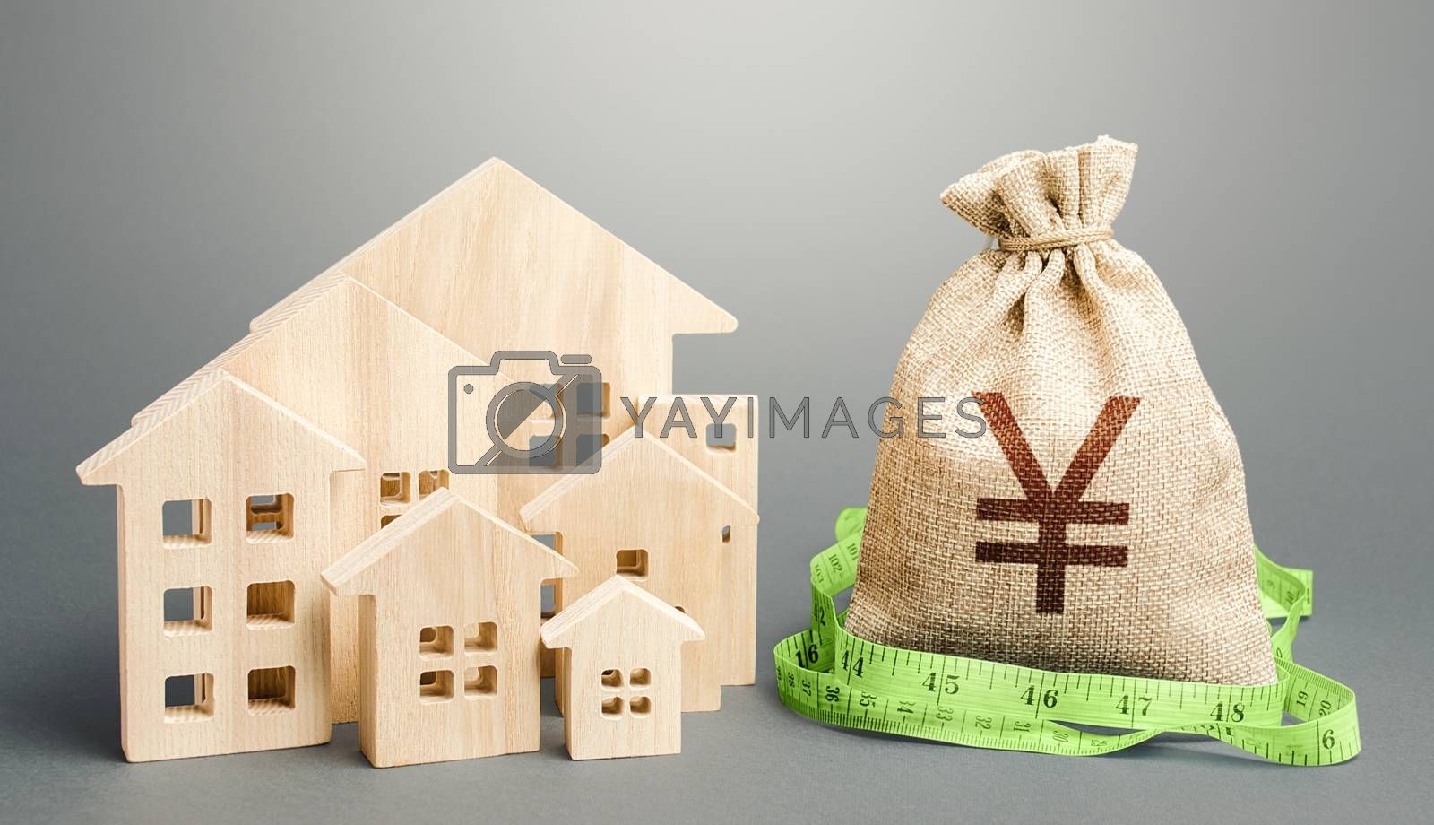 Residential houses and a Yen Yuan money bag. Buying, fair price. City municipal budget. Property real estate valuation. Mortgage loan. Calculation of construction and repair expenses