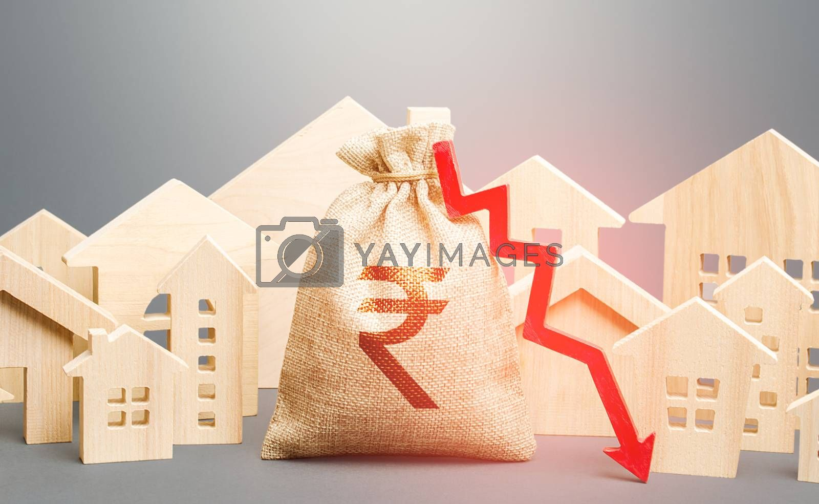 City residential buildings and indian rupee money bag with a red down arrow. Low cost of real estate. Falling prices for rental apartments. Low demand for home buying. Lower mortgage interest rates.