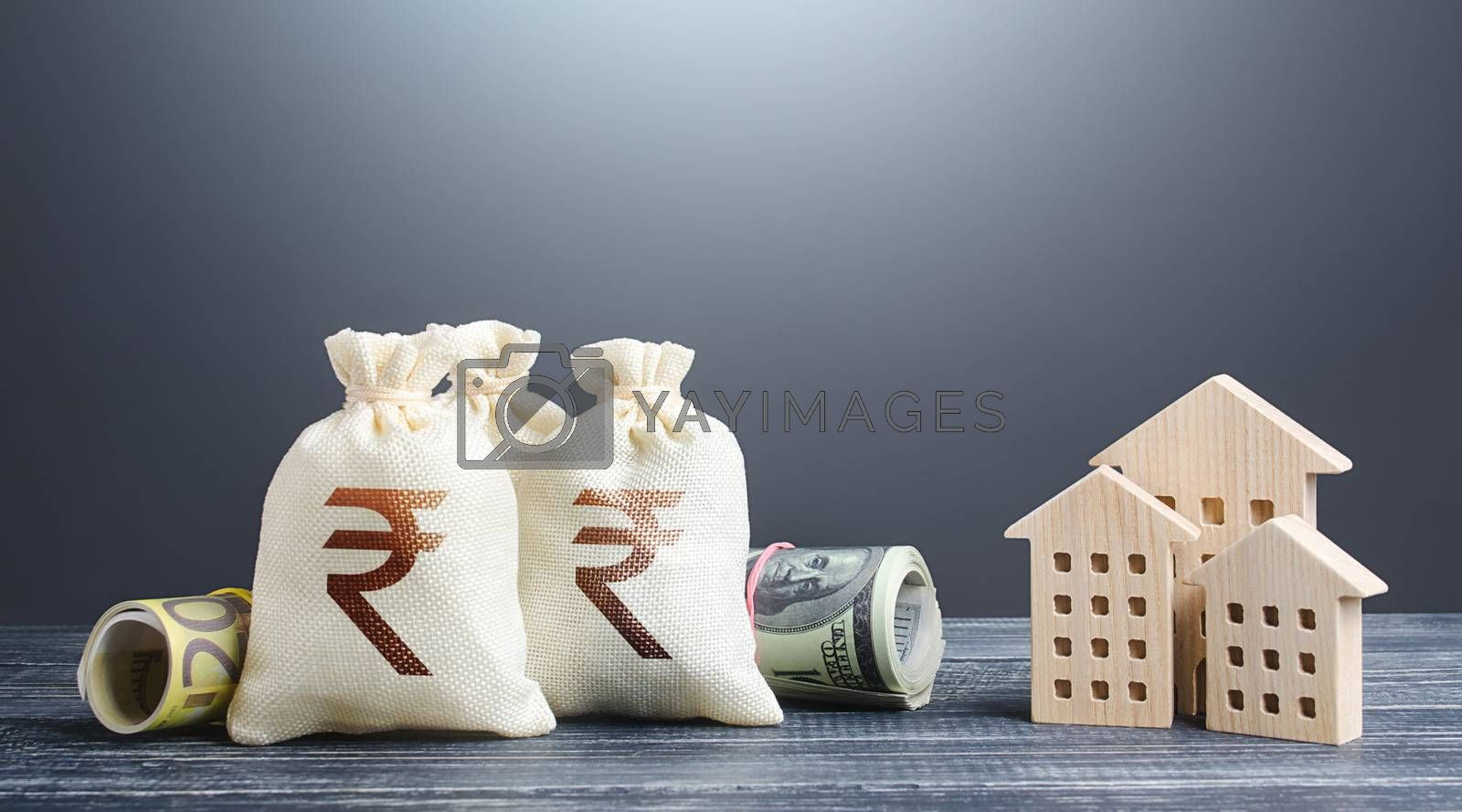 Indian rupee money bags and residential buildings figures. Investments in real estate. Mortgage loan. Financing the construction and renovation of housing. Municipal budget management. Taxes.