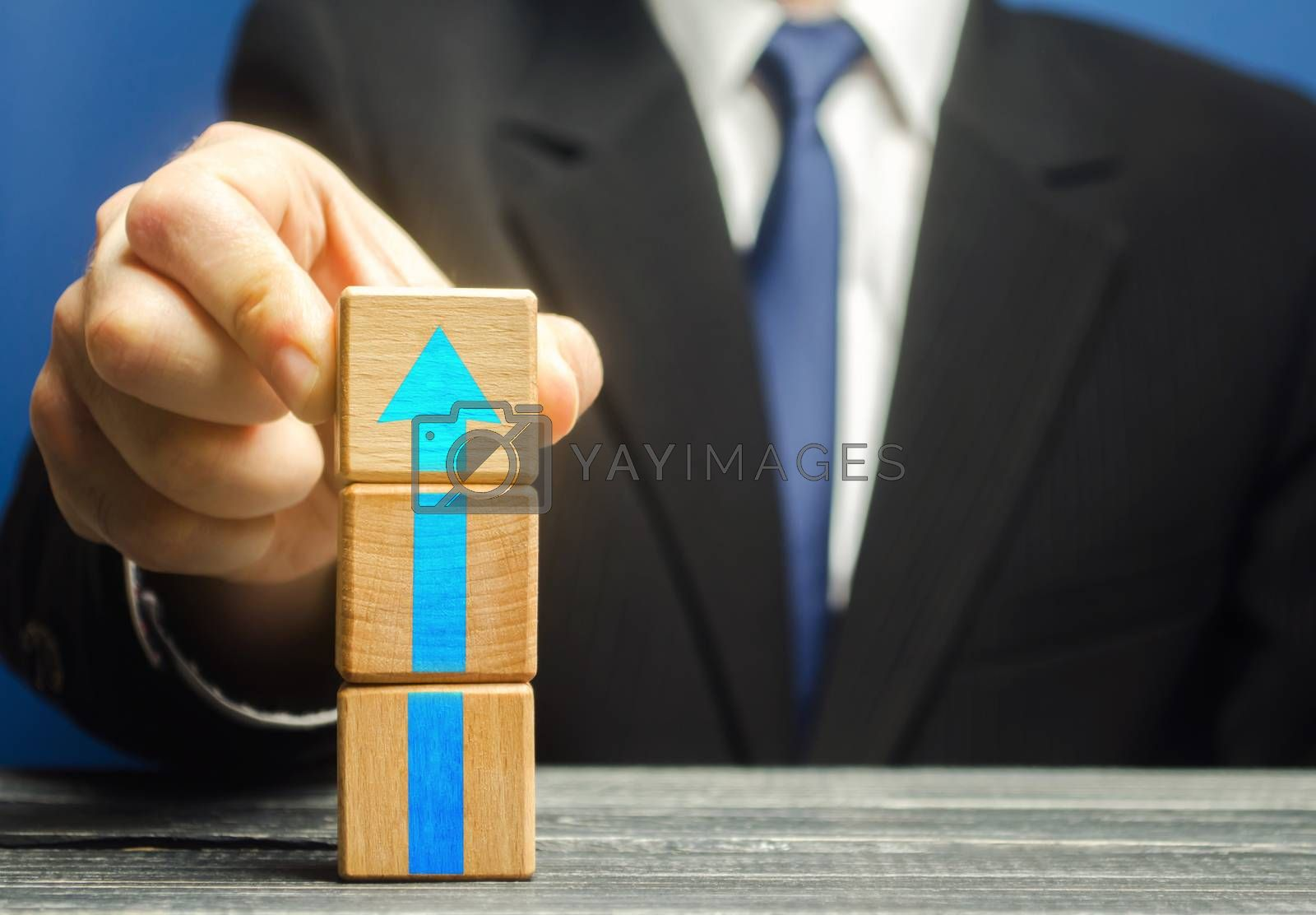 Businessman builds a tower of blocks with an up arrow. Career promotion , growth of professional skills. Business development, expansion improvement. Profit growth. Marketing. Improving efficiency