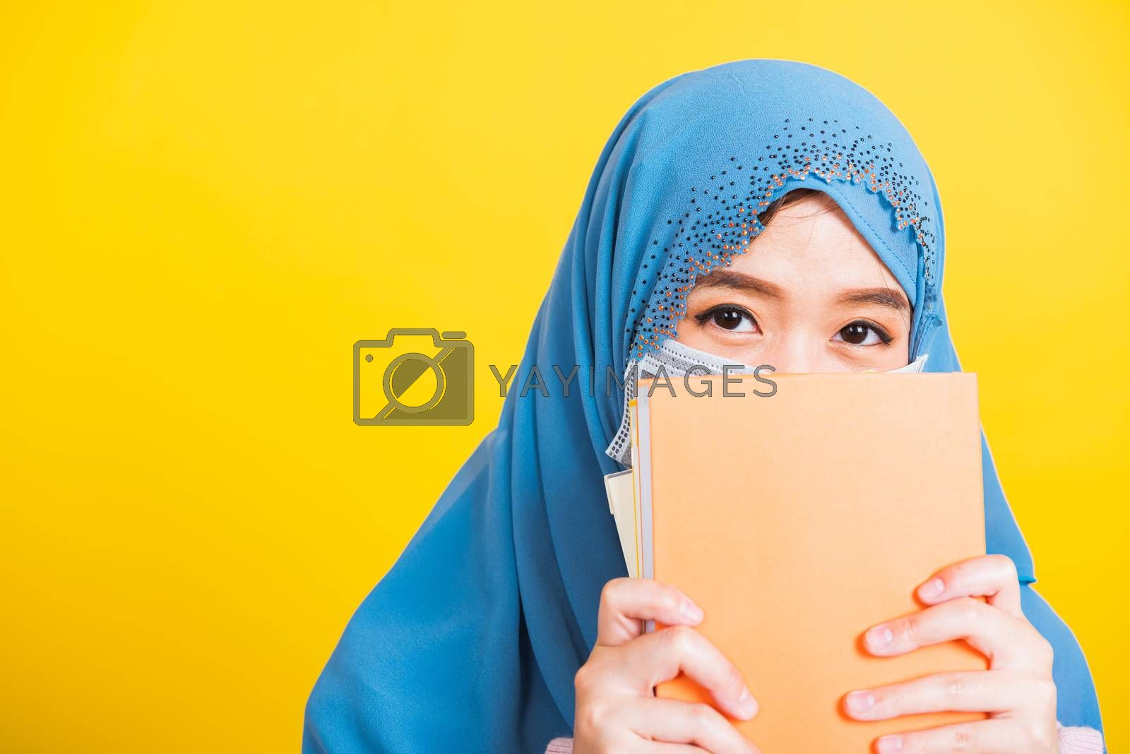 Asian Muslim Arab, Happy beautiful young woman religious wear veil hijab and face mask to prevent coronavirus she student hold books close face, isolated on yellow background, Back to college