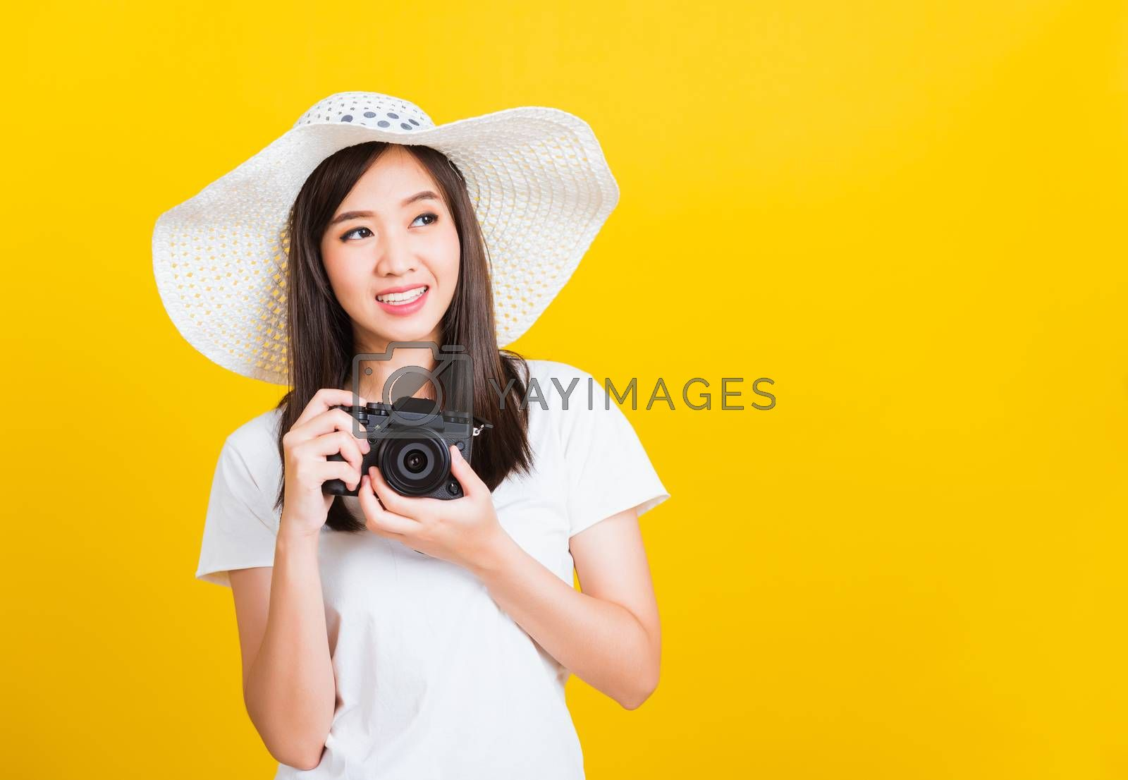 Portrait of happy Asian beautiful young woman photographer holding vintage digital mirrorless photo camera on hands, studio shot isolated on yellow background, lifestyle teenager hobby travel concept