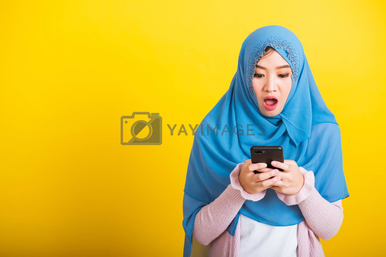 Asian Muslim Arab, Portrait of happy beautiful young woman Islam religious wear veil hijab funny smile she reads surprised confused shock news open mouth, studio shot isolated on yellow background