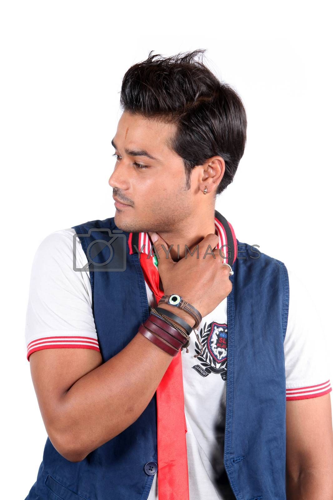 A handsome young Indian guy lost in his thoughts, on white studio background.