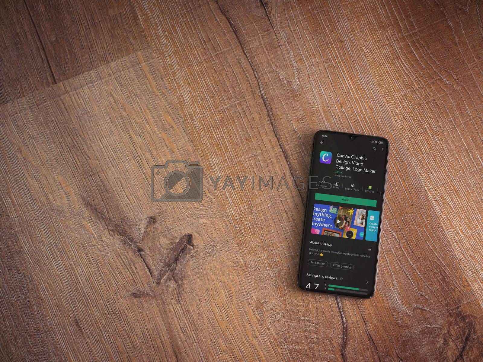 Lod, Israel - July 8, 2020: Canva - Graphic Design app play store page on the display of a black mobile smartphone on wooden background. Top view flat lay with copy space.