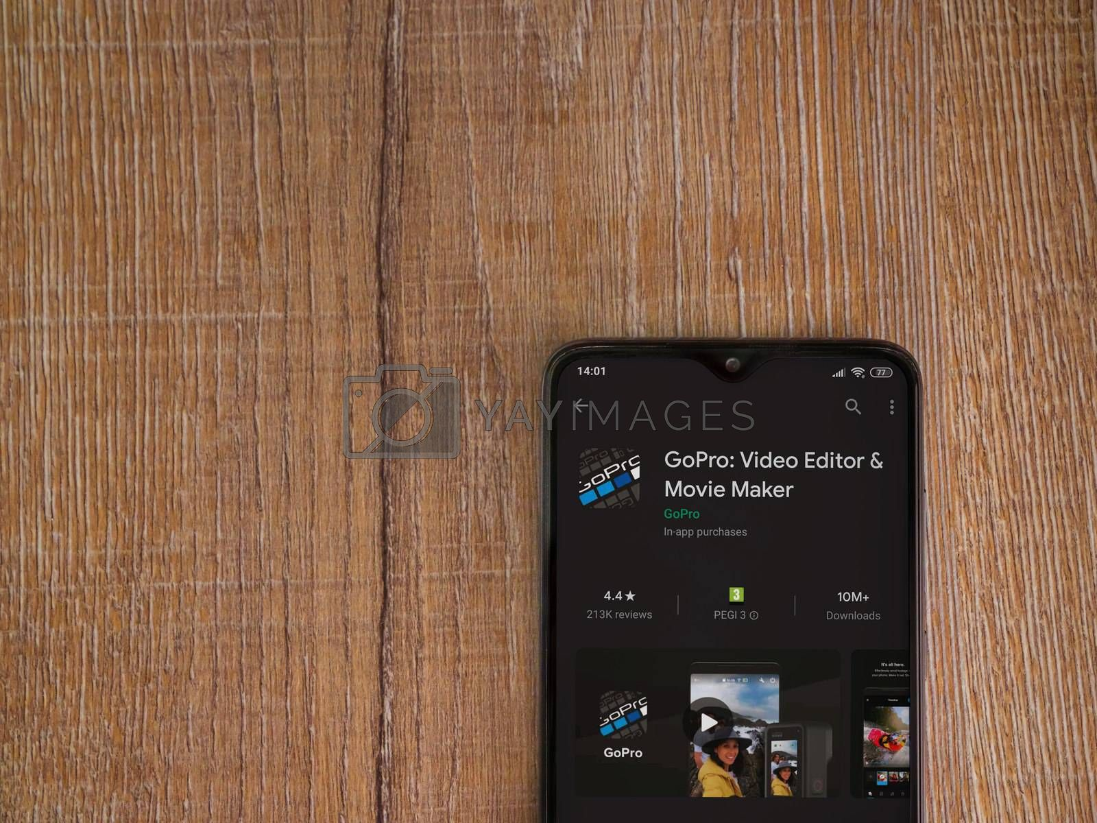 Lod, Israel - July 8, 2020: GoPro - Video Editor and Movie Maker app play store page on the display of a black mobile smartphone on wooden background. Top view flat lay with copy space.