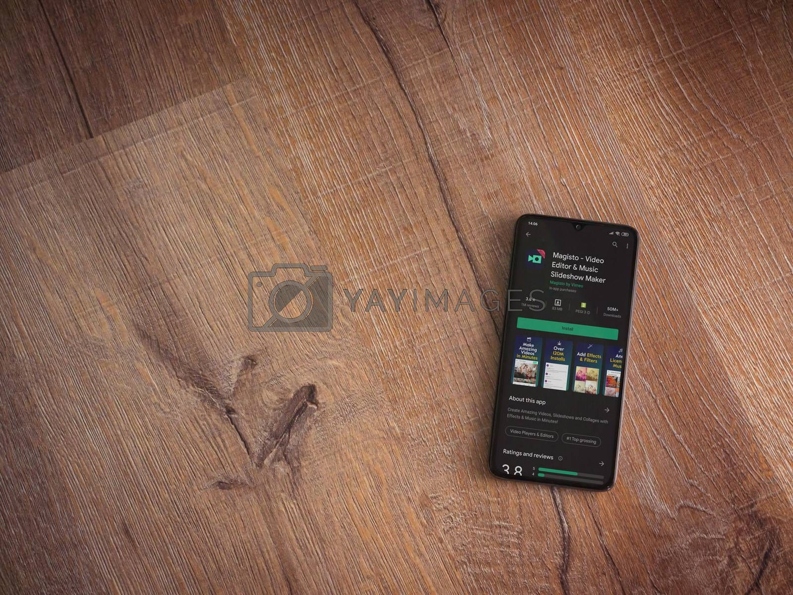 Lod, Israel - July 8, 2020: Magisto - Video Editor and Movie Maker app play store page on the display of a black mobile smartphone on wooden background. Top view flat lay with copy space.