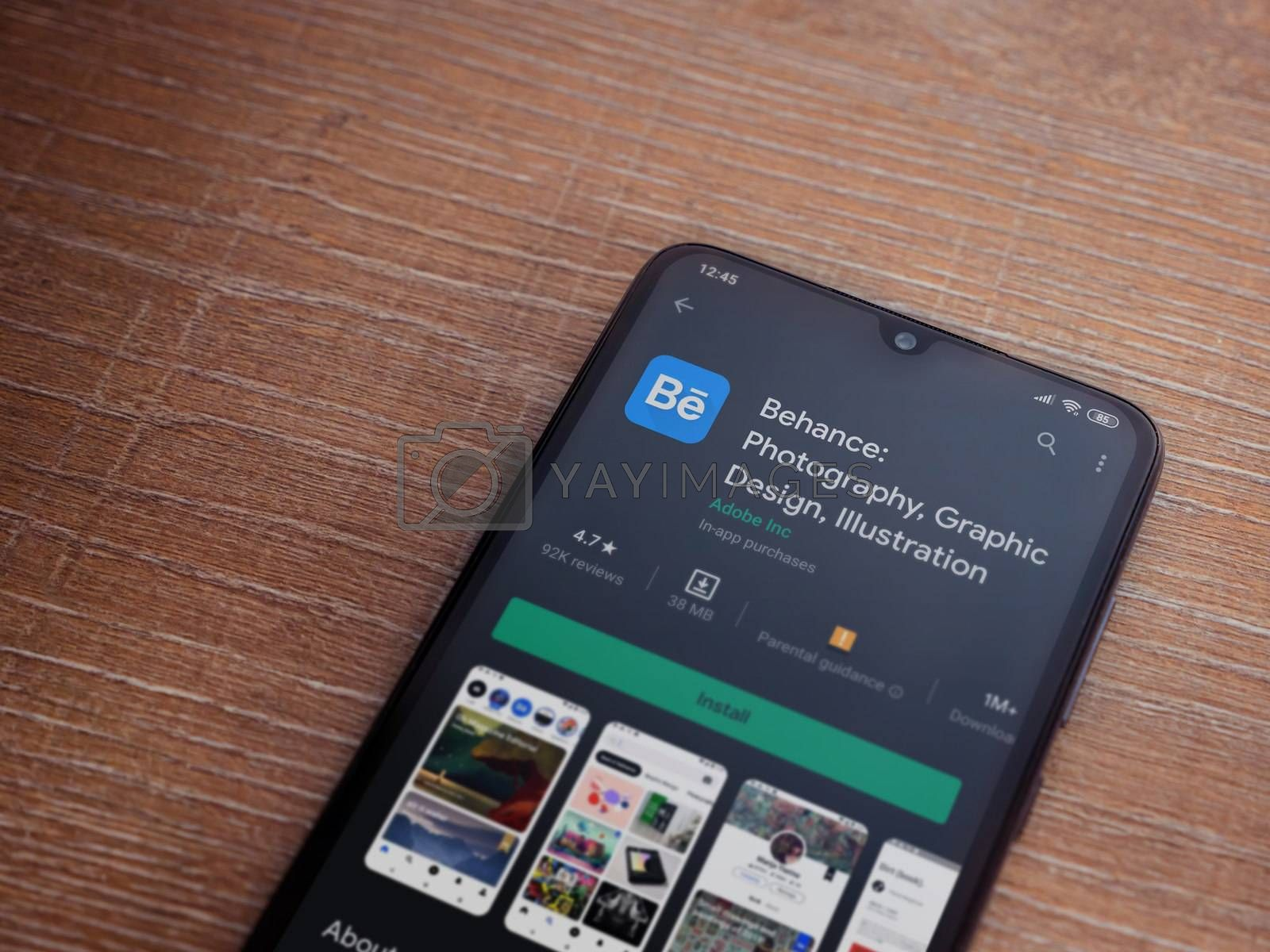 Lod, Israel - July 8, 2020: Adobe Behance app play store page on the display of a black mobile smartphone on wooden background. Top view flat lay with copy space.