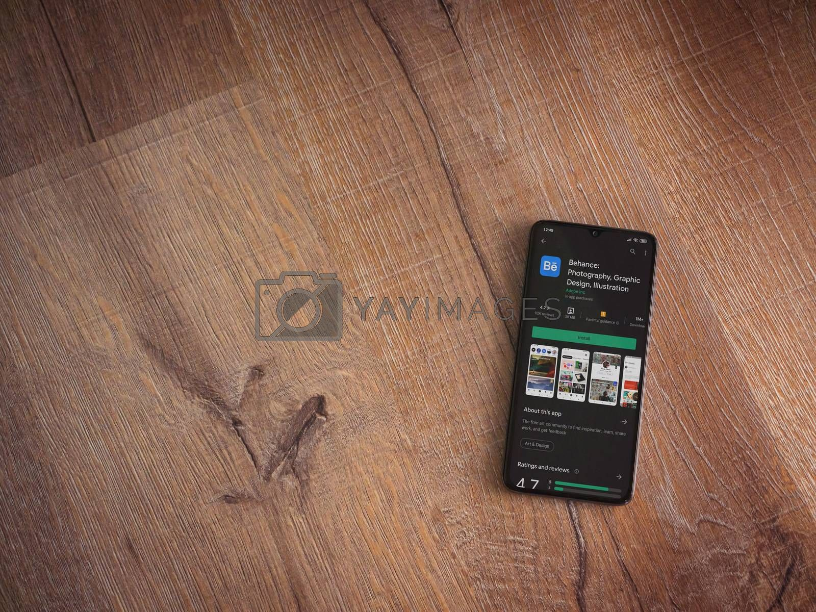 Adobe Behance app play store page on the display of a black mobi by Wave Movies