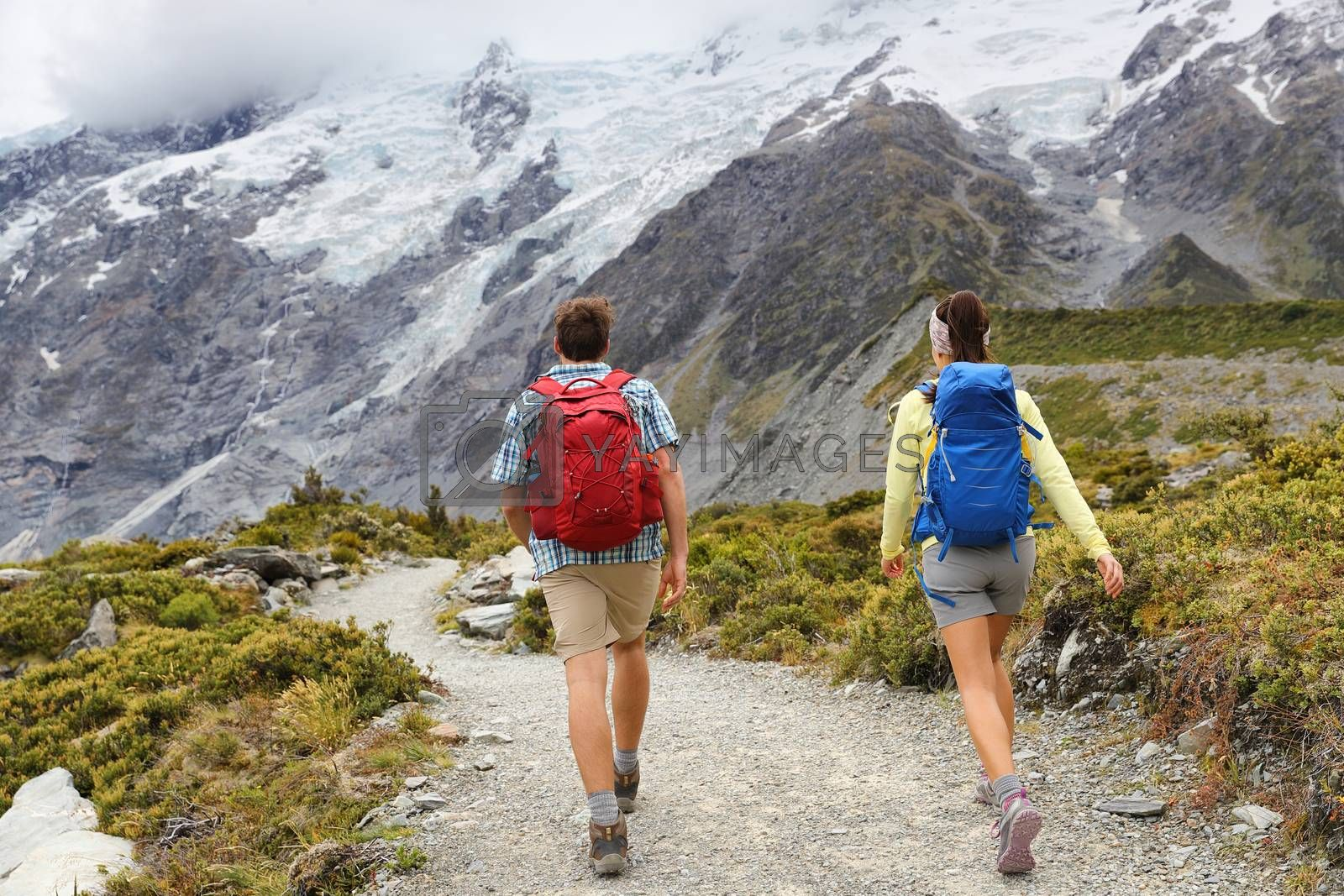 New Zealand travel tramping hikers walking on trail of Hooker Valley Track in New Zealand Aoraki/Mt Cook. Couple tourists hiking in mountains on popular tourist destination. Kiwi trampers with bags.