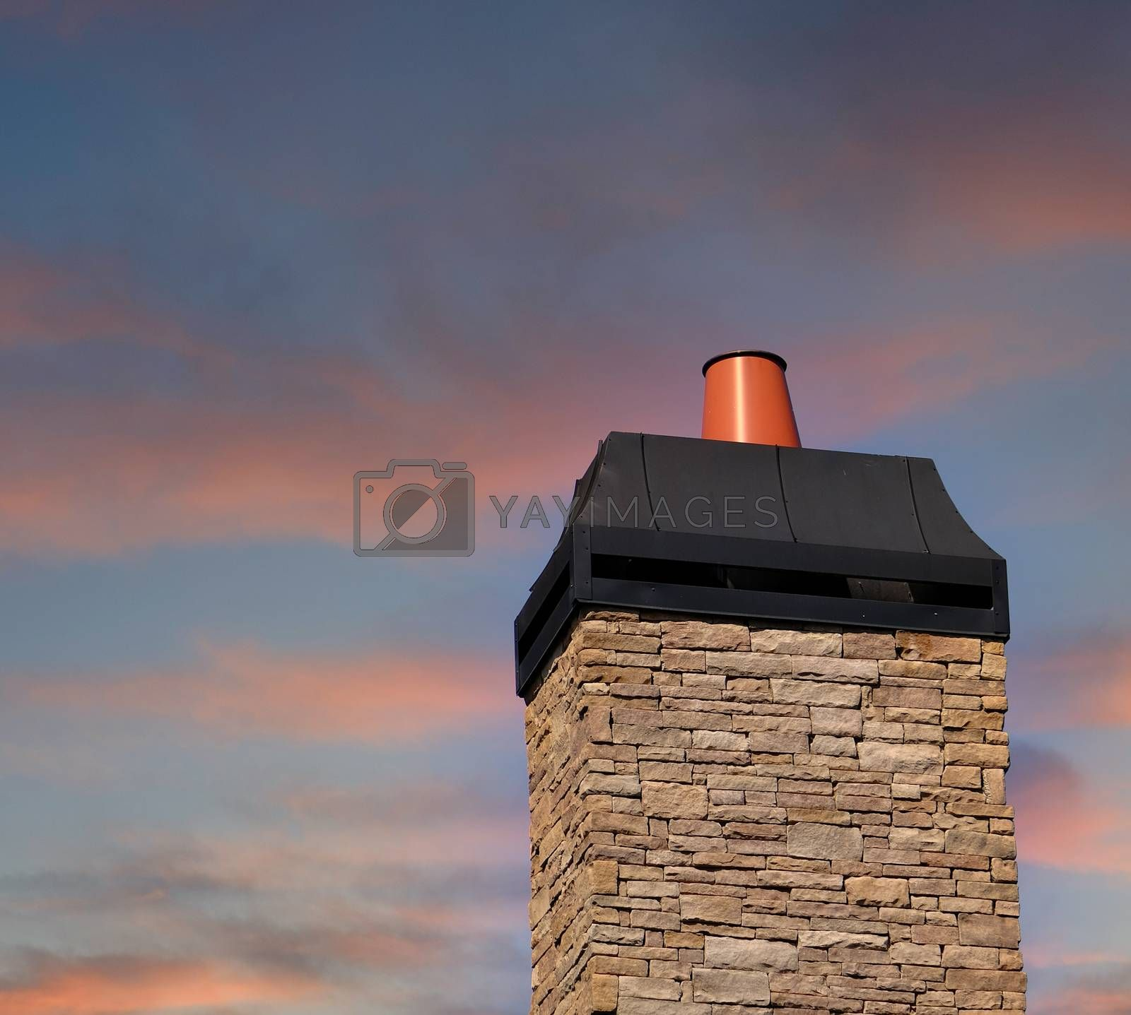 Stone Chimeny with Metal Cap Afainst a Clear Blue Sky