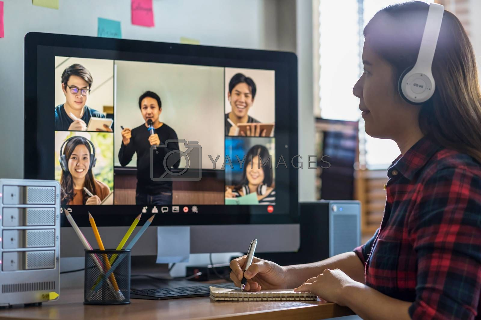 Closeup Asian woman hand writing lecture when online learning via video conference with teacher or speaker with colleague when Covid-19 pandemic, Coronavirus outbreak,online meeting,new normal concept