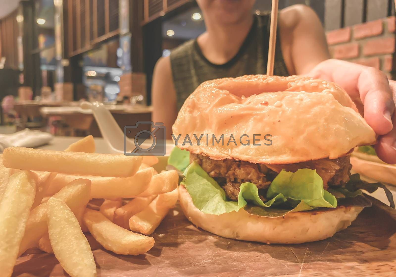 Woman trying to pick up hamburger and french fries on the wood table.Junk food and cholesterol. Close up and blur.
