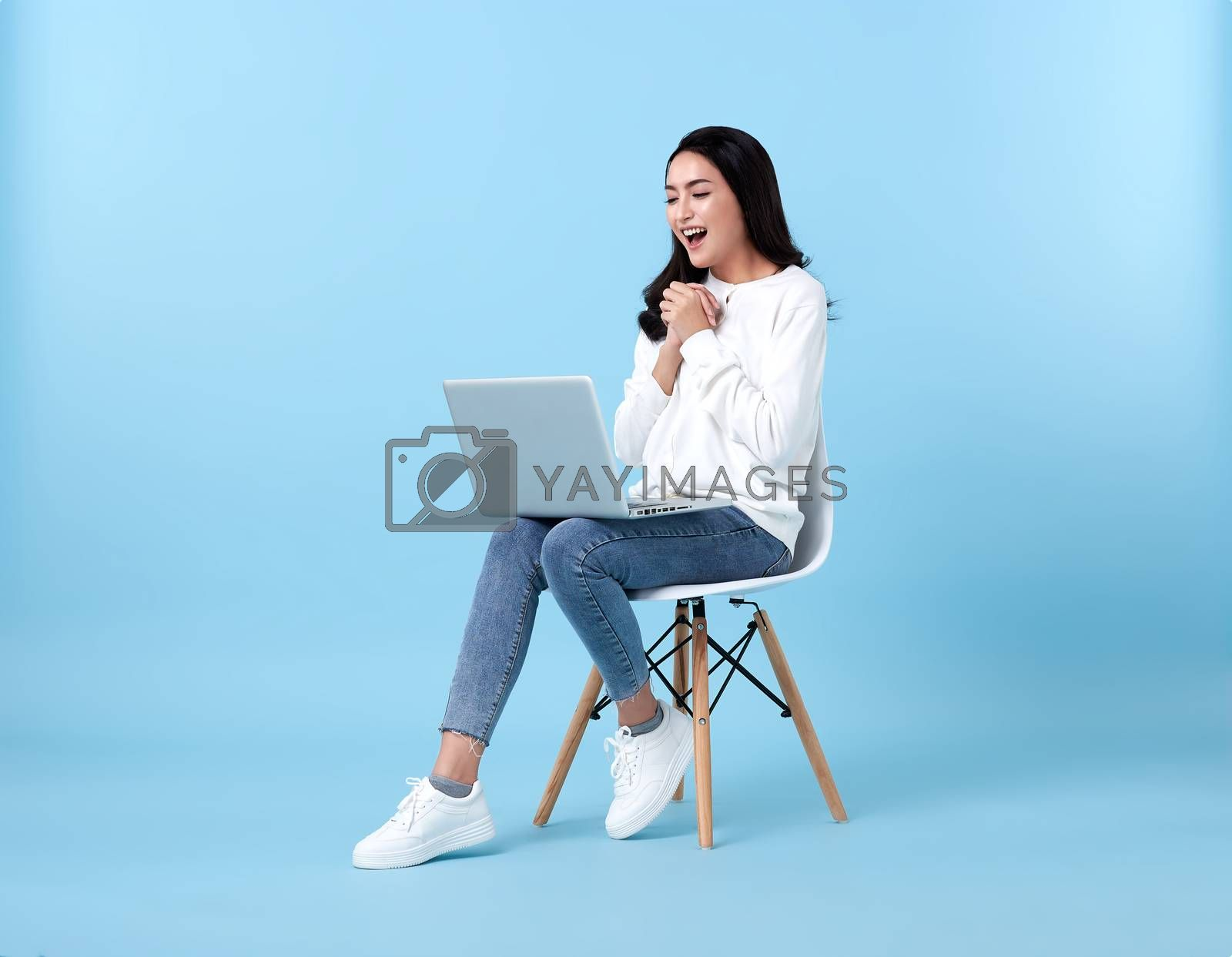 Young woman asian happy smiling in casual white cardigan with denim jeans.While her using laptop sitting on white chair isolate on bright blue background.
