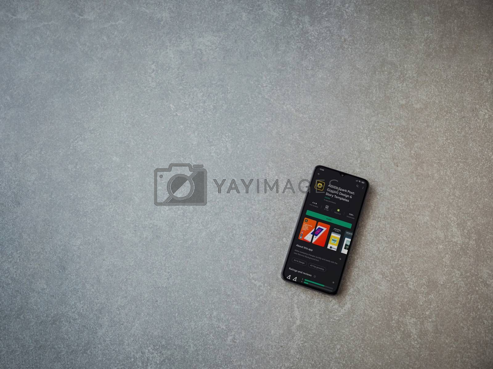 Lod, Israel - July 8, 2020: Adobe Spark Post - Graphic Design and Story Templates app play store page on the display of a black mobile smartphone on ceramic stone background.Top view flat lay with copy space