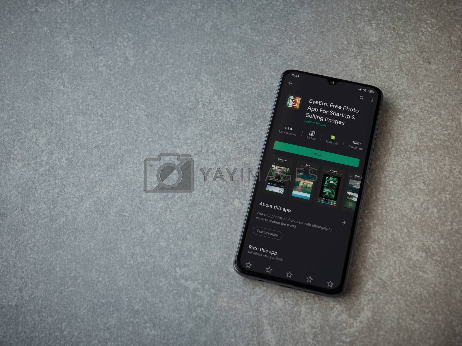 Lod, Israel - July 8, 2020: EyeEm - Sharing and Selling Images app play store page on the display of a black mobile smartphone on ceramic stone background. Top view flat lay with copy space.