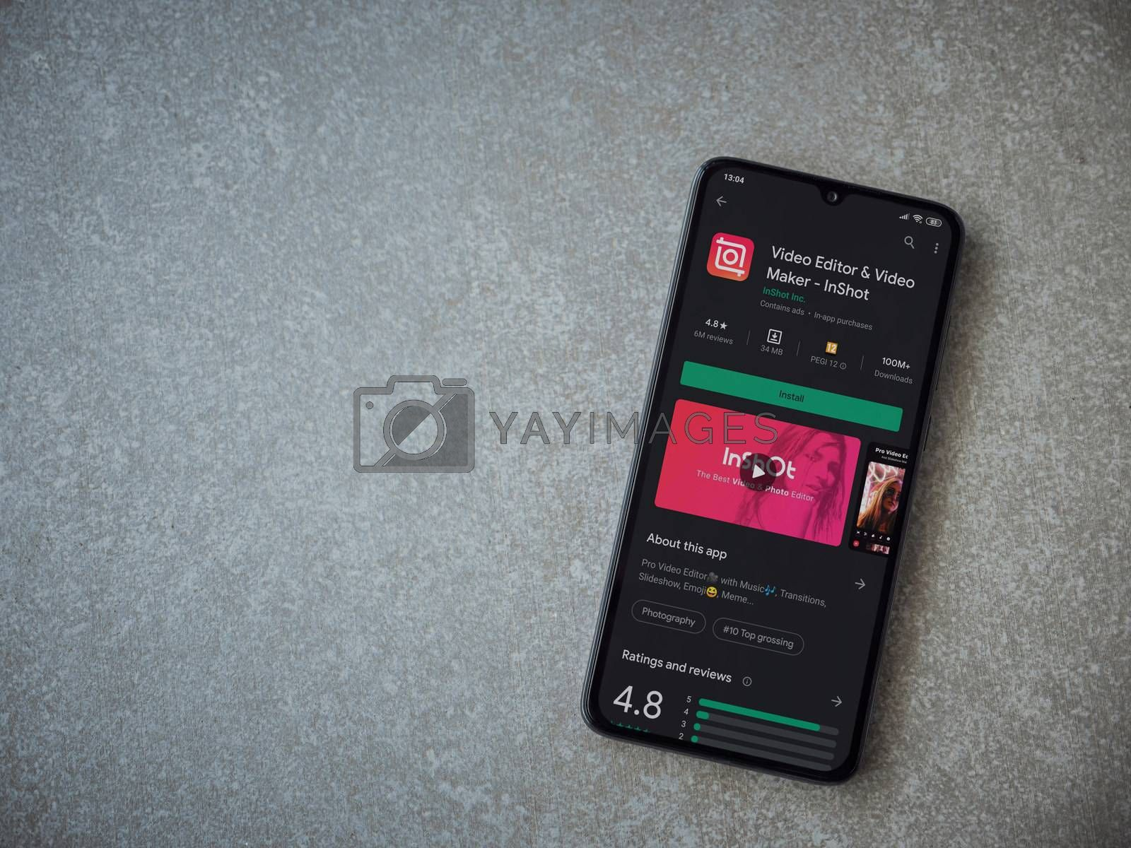 Lod, Israel - July 8, 2020: InShot - Video Editor and Movie Maker app play store page on the display of a black mobile smartphone on ceramic stone background. Top view flat lay with copy space.