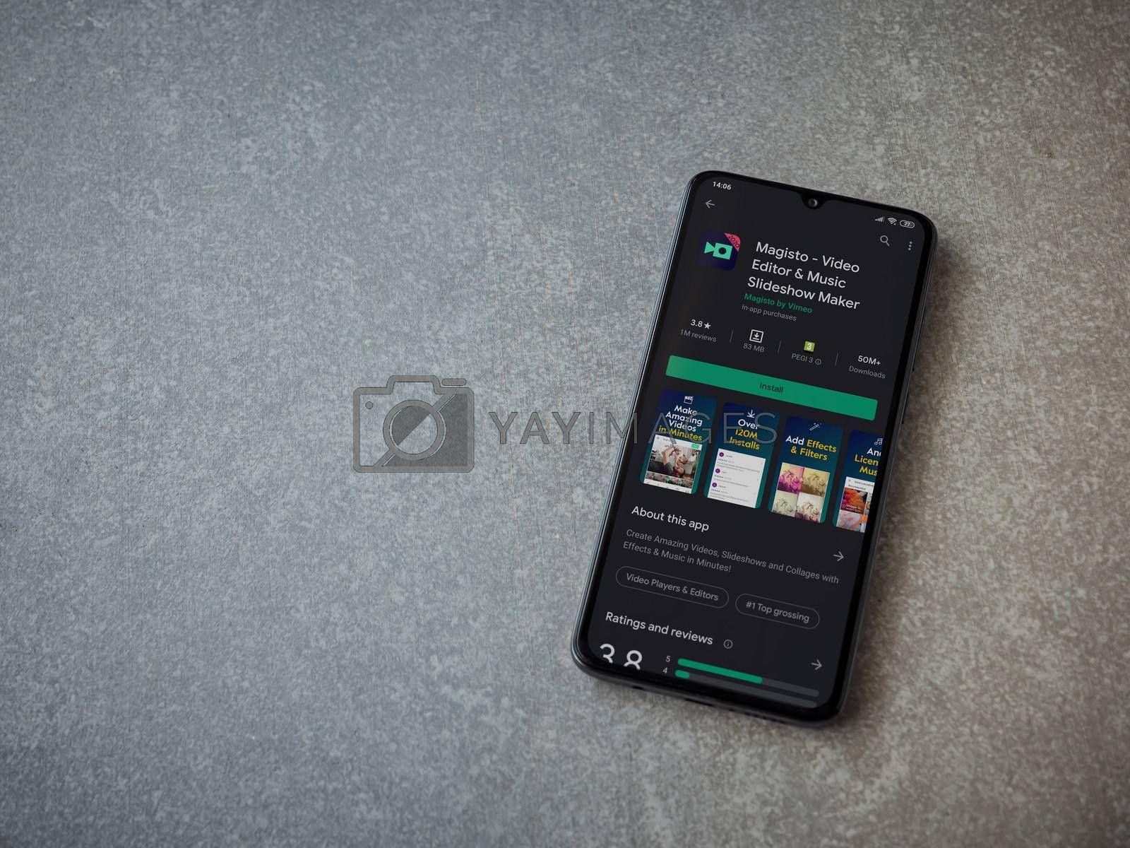 Lod, Israel - July 8, 2020: Magisto - Video Editor and Movie Maker app play store page on the display of a black mobile smartphone on ceramic stone background. Top view flat lay with copy space.