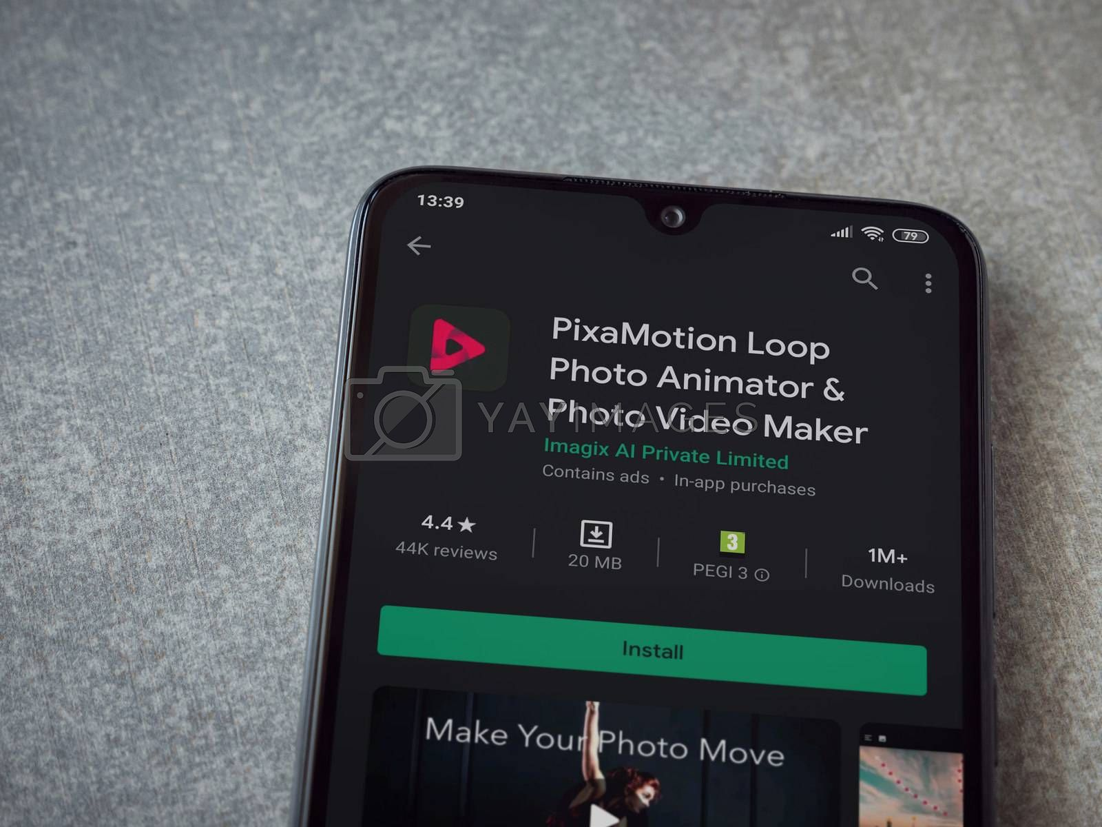 Lod, Israel - July 8, 2020: PixaMotion app play store page on the display of a black mobile smartphone on ceramic stone background. Top view flat lay with copy space.