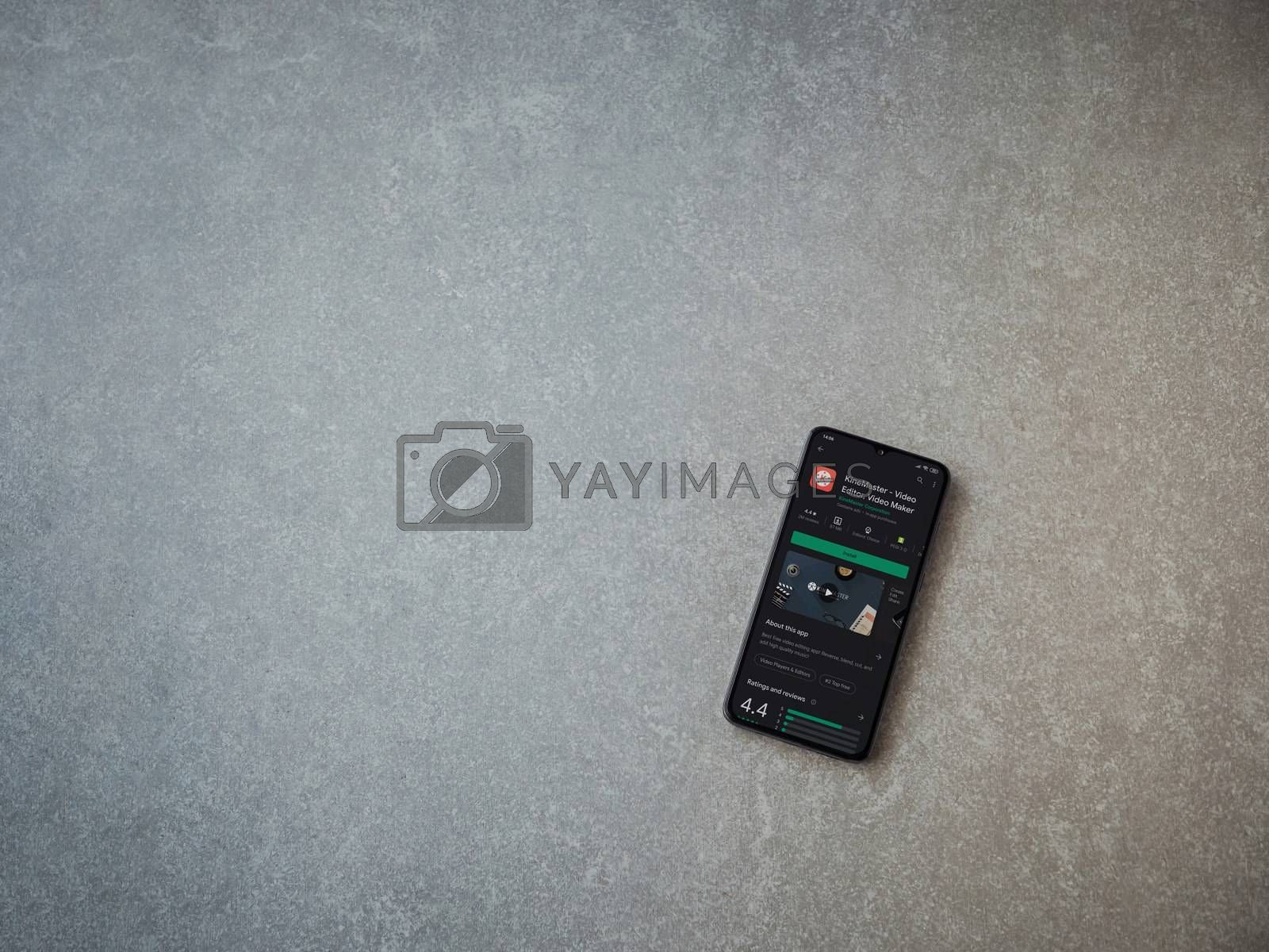 Lod, Israel - July 8, 2020: KineMaster - Video Editor and Movie Maker app play store page on the display of a black mobile smartphone on ceramic stone background. Top view flat lay with copy space.