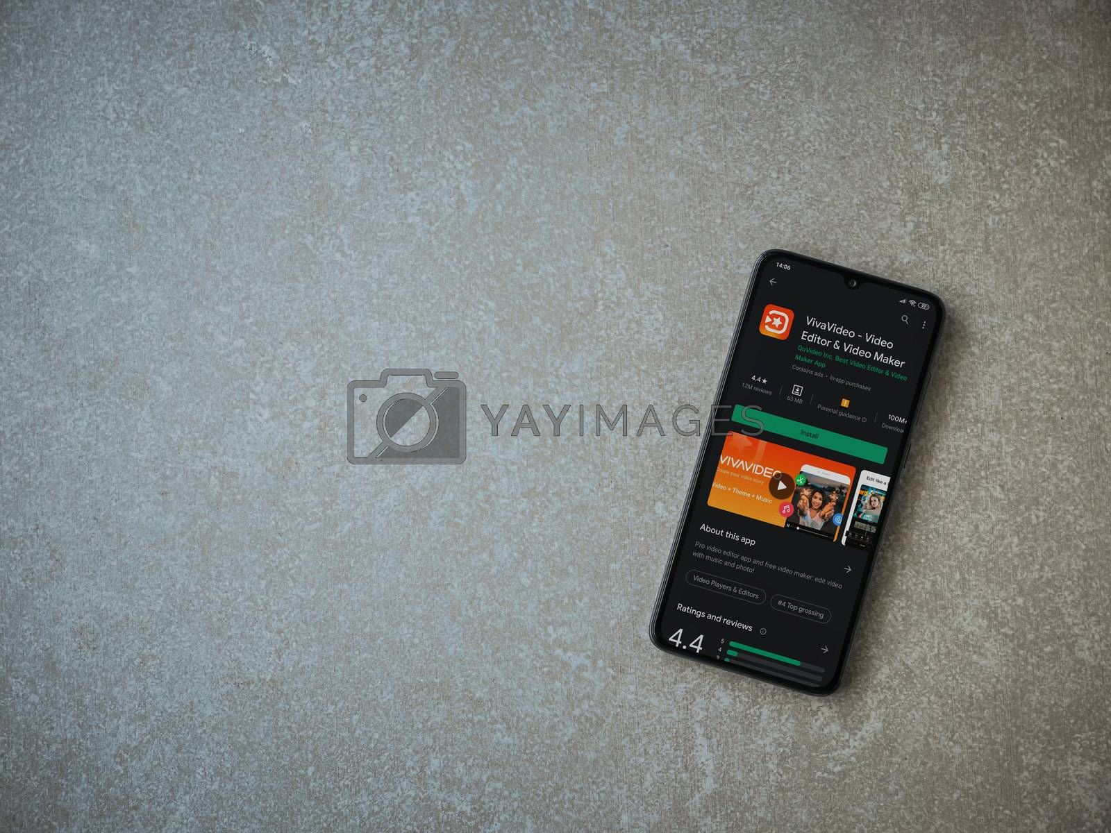 Lod, Israel - July 8, 2020: VivaVideo - Video Editor and Movie Maker app play store page on the display of a black mobile smartphone on ceramic stone background. Top view flat lay with copy space.