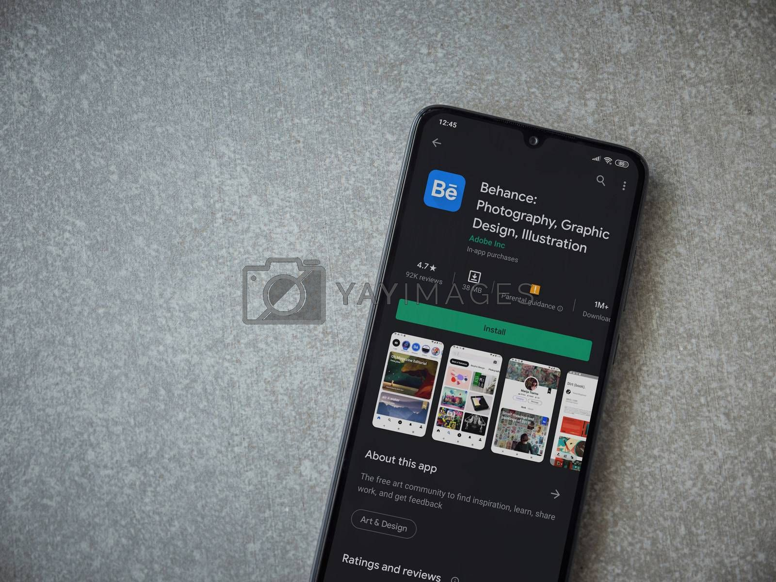 Lod, Israel - July 8, 2020: Adobe Behance app play store page on the display of a black mobile smartphone on ceramic stone background. Top view flat lay with copy space.
