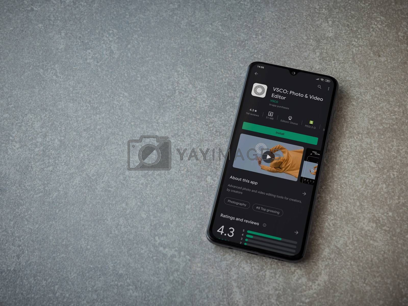 Lod, Israel - July 8, 2020: VSCO - Photo and Video Editor app play store page on the display of a black mobile smartphone on ceramic stone background. Top view flat lay with copy space.