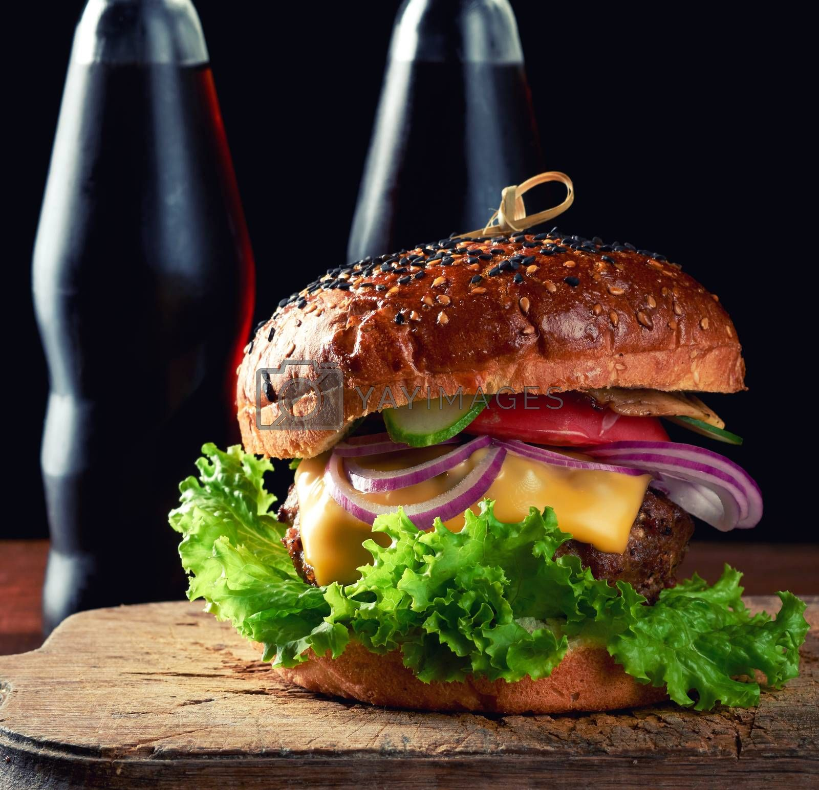 delicious burger with fried beef cutlet, tomato, lettuce and onions, crispy white wheat flour bun with sesame seeds. Fast food on a wooden board, behind a bottle with a drink