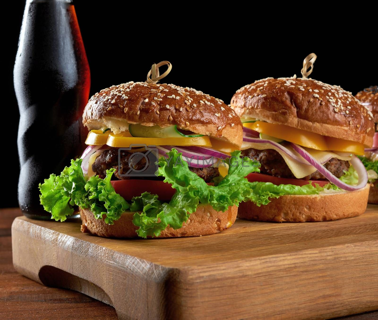 delicious burgers with fried beef cutlet, tomato, lettuce and onions, crispy white wheat flour bun with sesame seeds. Fast food on a wooden board, behind a bottle with a drink